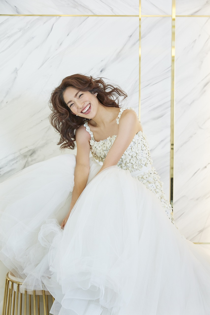 望月芹名さんが着ているドレスは3Dのフラワーモチーフが付いたヴィクター&ロルフ・マリアージュの白いウェディングドレスドレス