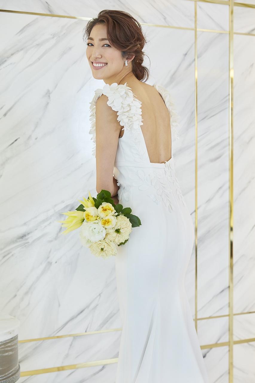 望月芹名さんが着ているドレスは3Dの藤の花のモチーフが付いたヴィクター&ロルフ・マリアージュの白いウェディングドレスドレス