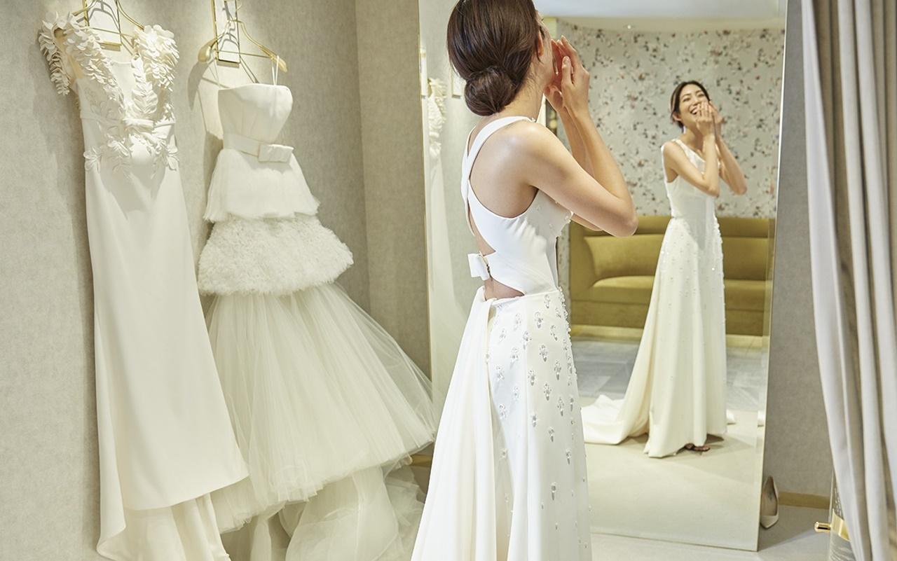 ヴィクター&ロルフ・マリアージュのウェディングドレスを着てフィッティングルームの鏡でほほ笑む望月芹名さん