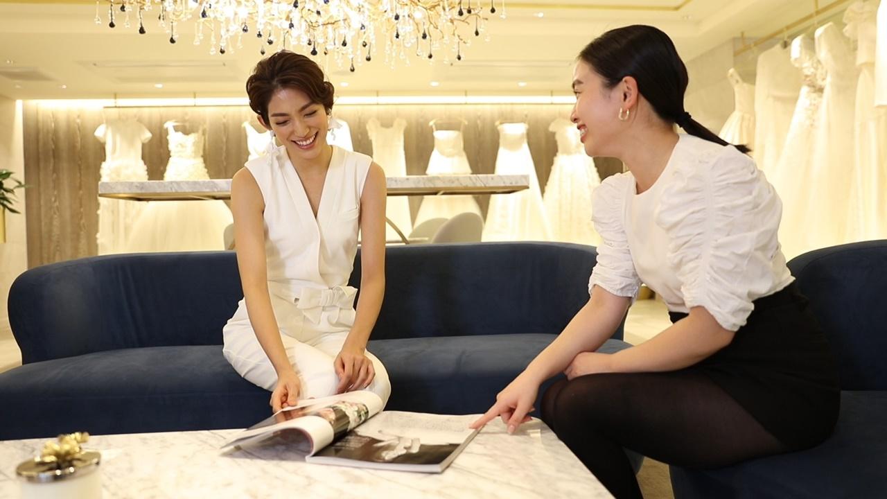 白いVネックカットのヴィクター&ロルフ・マリアージュのパンツスタイルのウェディングドレスを身に纏った望月芹名さんとPR飯島