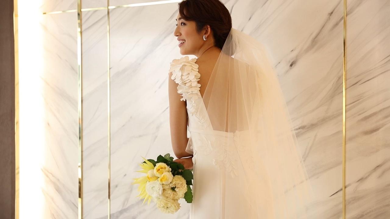 3Dの藤の花のモチーフが付いたヴィクター&ロルフ・マリアージュのウェディングドレスを身に纏いベールを合わせたスタイルの望月芹名さん
