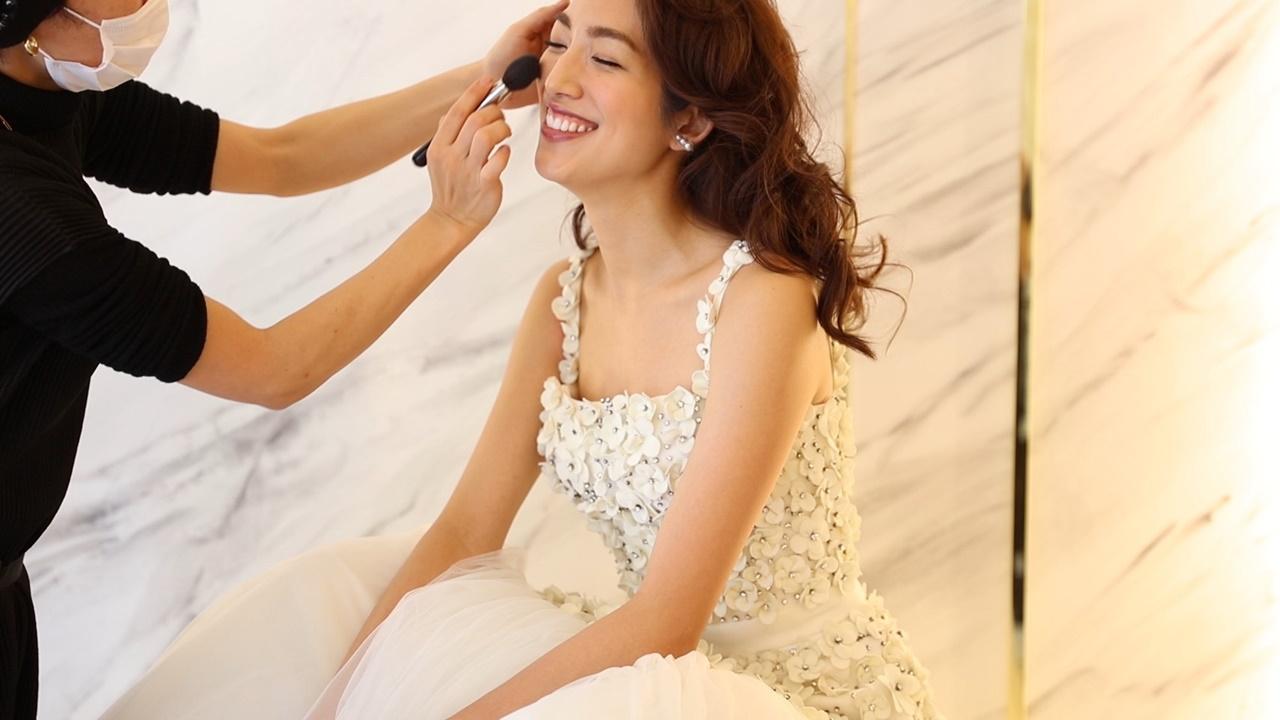 ヴィクター&ロルフ・マリアージュの3Dフラワーが付いた白いウェディングドレスを身に纏った望月芹名さん