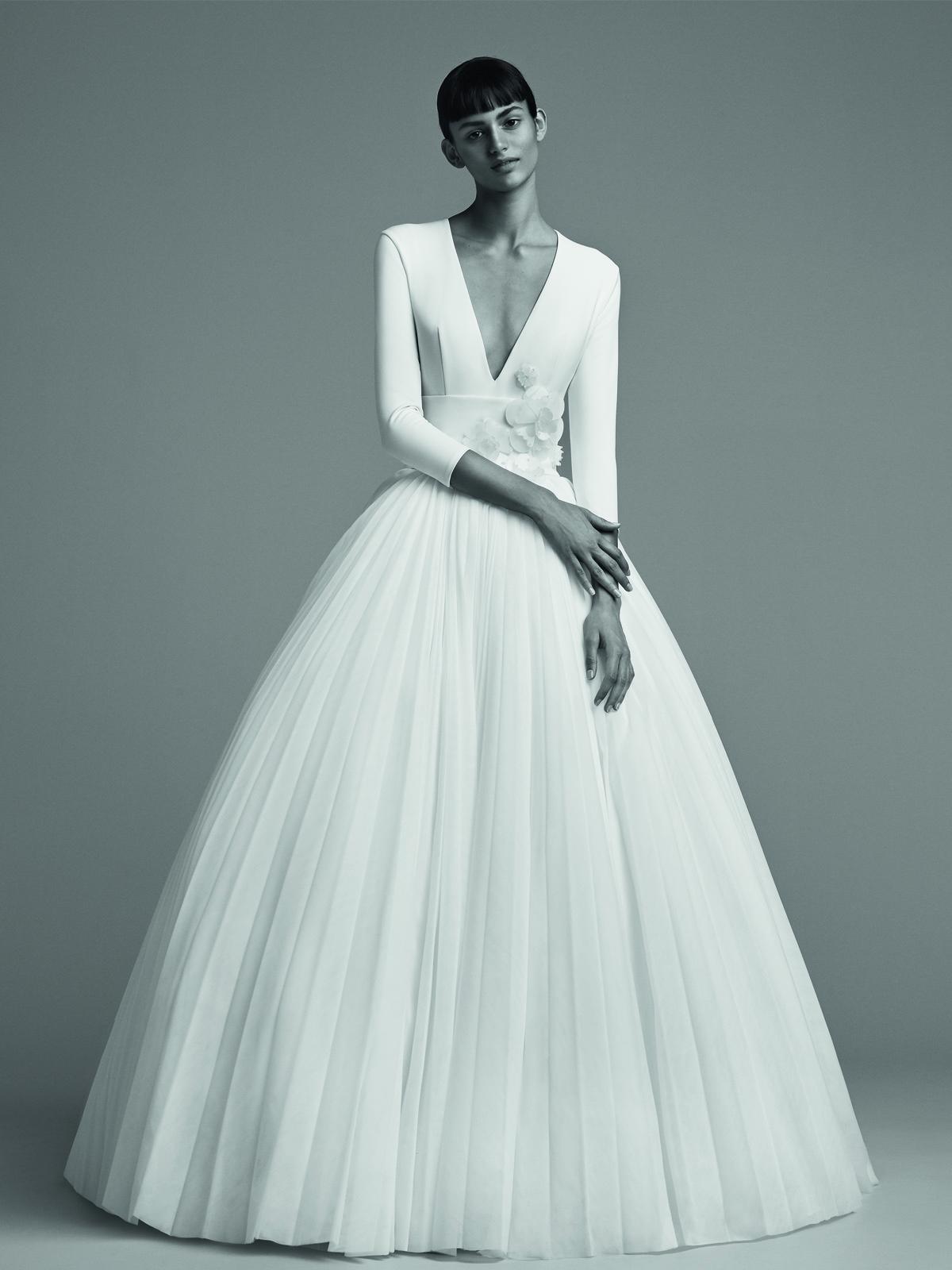 胸元がVカットでスカートには何重ものチュールが重なったプリンセルラインのヴィクター&ロルフ・マリアージュの白いウェディングドレス