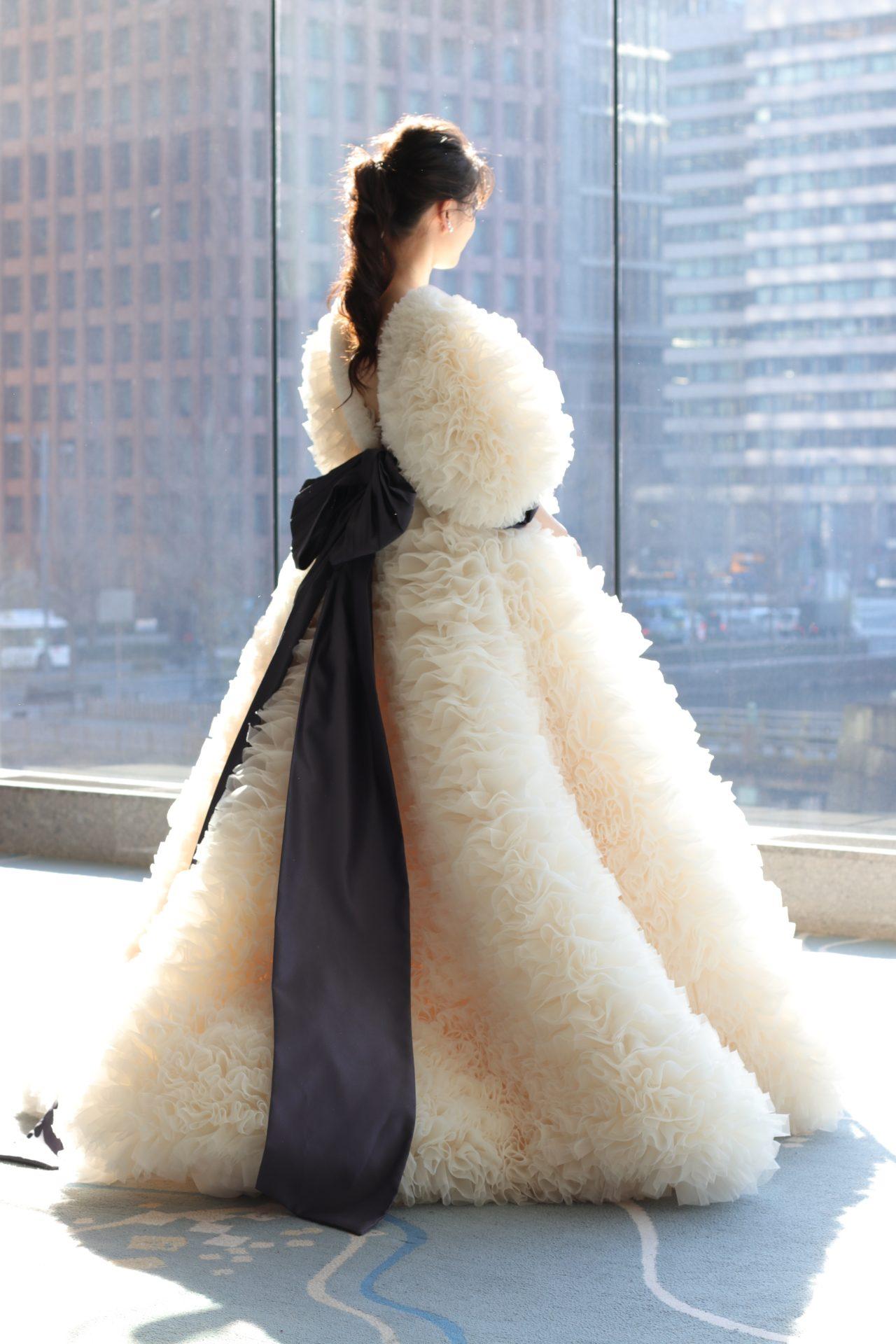 ホテルウェディングをお考えの東京のお洒落花嫁様におススメしたい新作ドレスは、オープンバックデザインと腰元から広がるバックリボンが印象的なTOMOKOIZUMIとTREATMAISONの新作コラボレーションドレスです