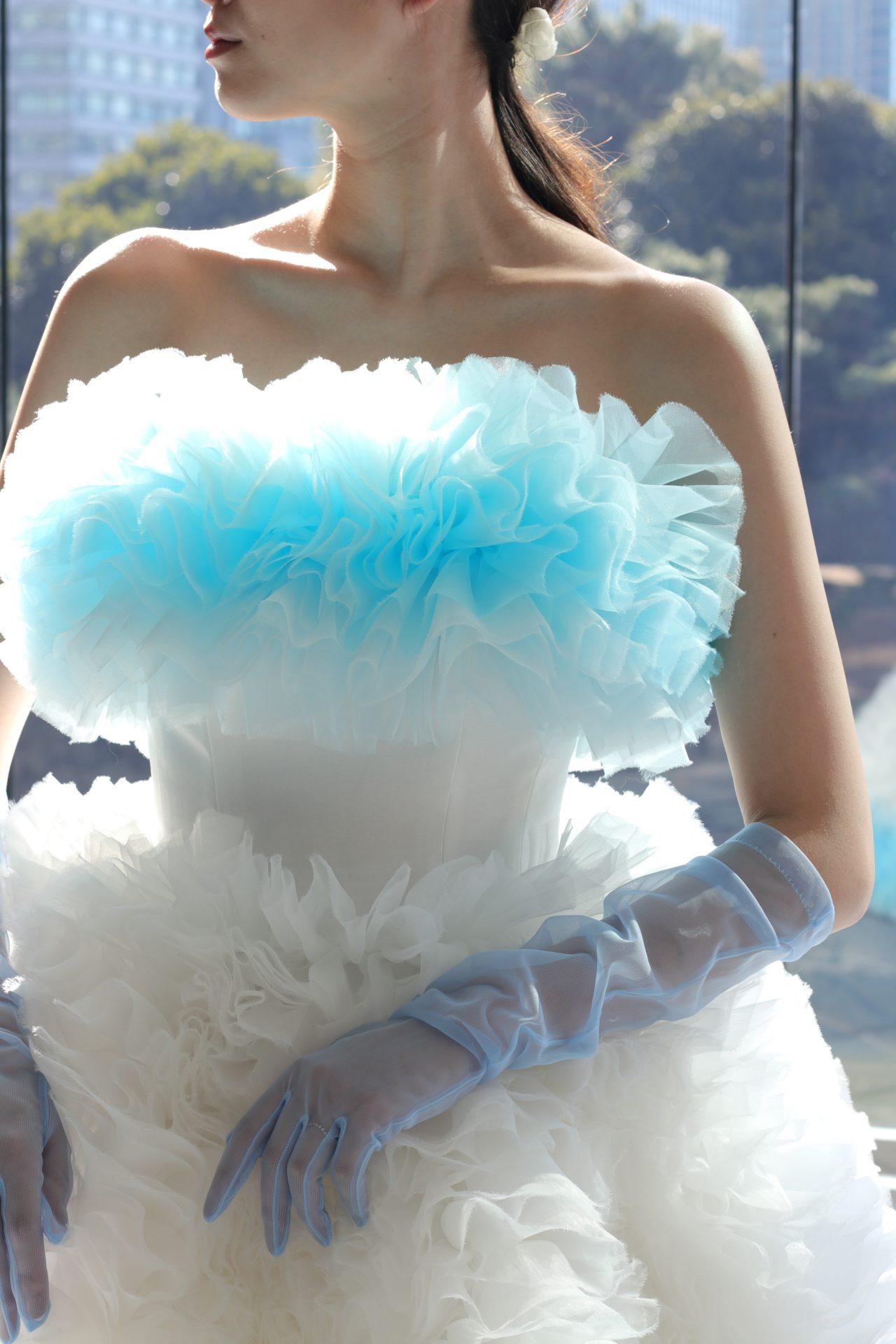トモコイズミとトリートメゾンが手掛ける新作カラードレスは、ホワイトからブルーへとグラデーションになった、胸元を覆う柔らかなフリルが美しく、ブルーのグローブとの相性もぴったりです