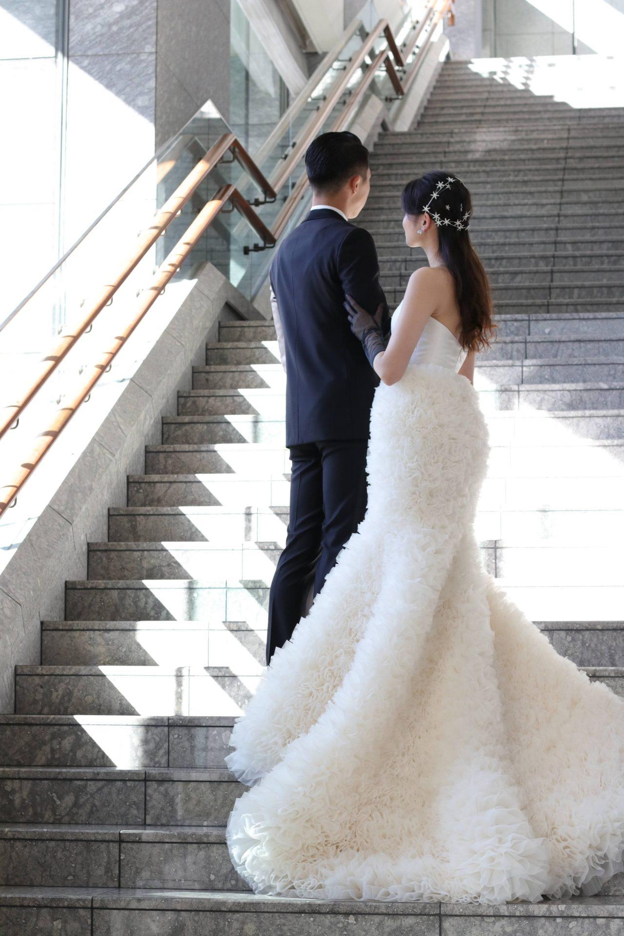 パレスホテル東京の大階段で撮る前撮りなら、立体的なシルエットが美しいマーメイドドレスとクラシックなネイビーのタキシードをあわせる事で、洗練されたお写真が残せます