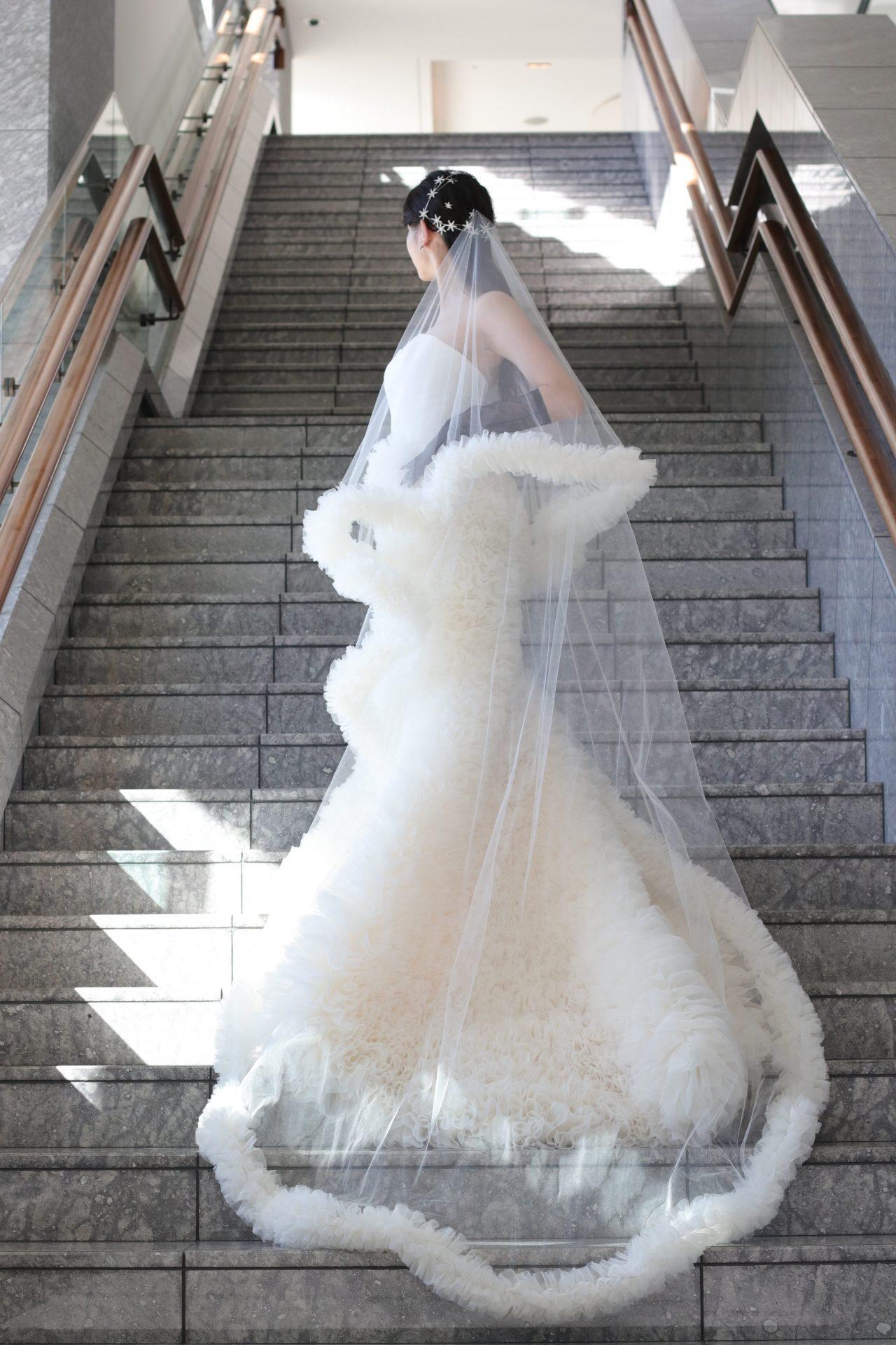前撮りをお考えの花嫁様にお勧めしたいマーメイドラインのウェディングドレスは、大理石の大階段に映えるようなロングトレーンと、ボリューミーなフリルスカートによるシルエットが美しく、ゴージャスなお写真を残すことが出来ます