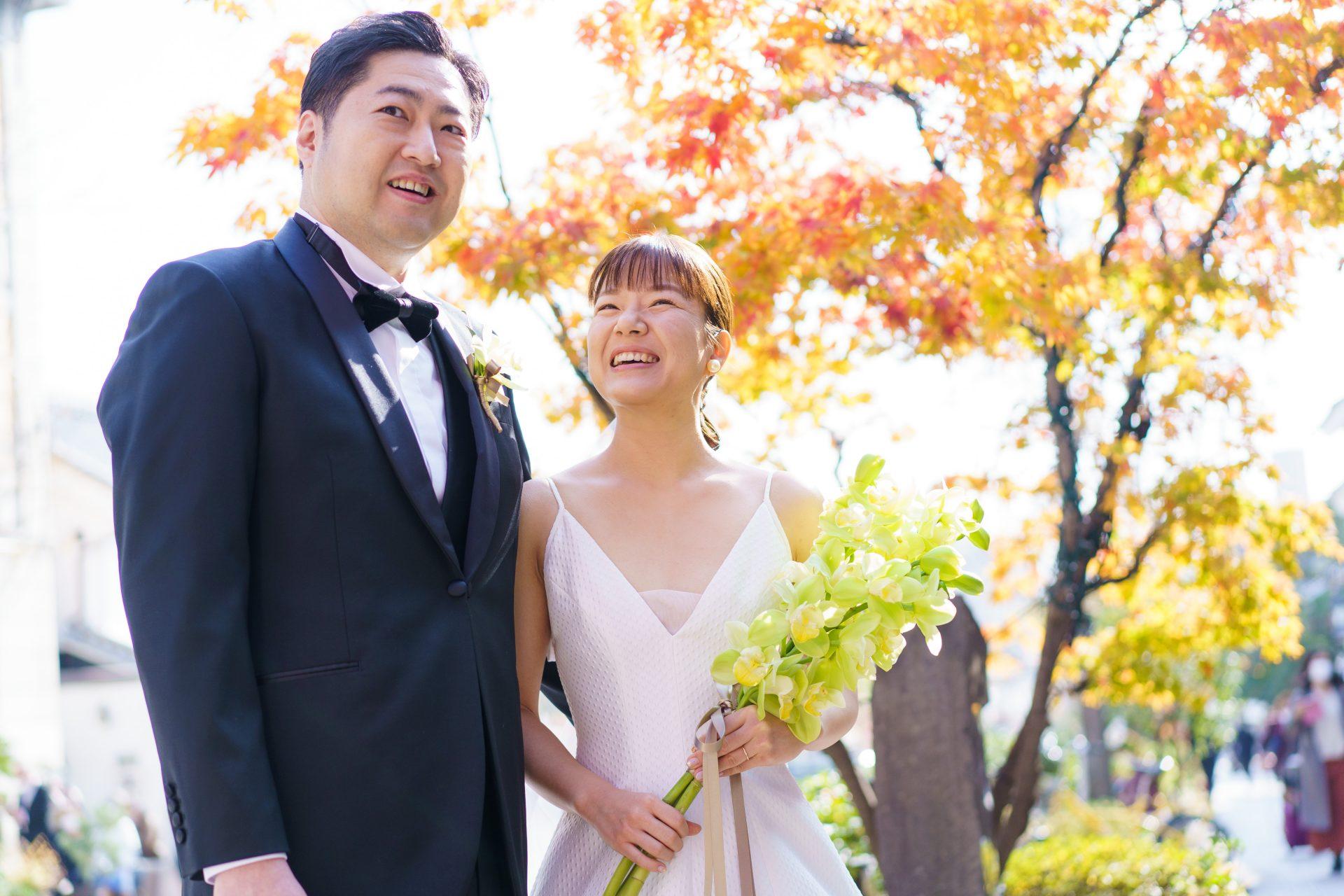 美しい紅葉の中でTHE TREAT DRESSINGのブラックフォーマルのタキシードとAラインのウェディングドレスを身に纏うご新郎様ご新婦様