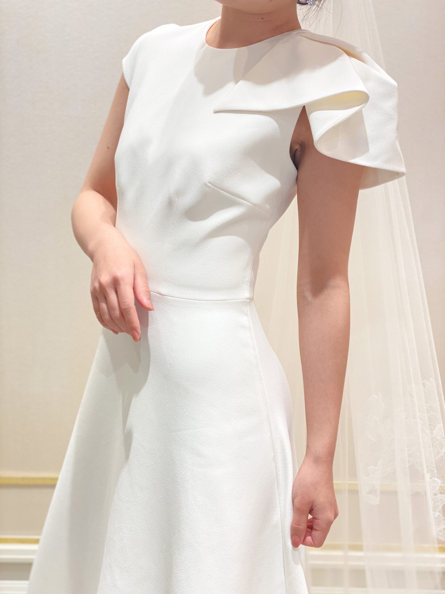 関西大阪にあるインポートウェディングドレスショップ、ザトリートドレッシングよりインポートドレスブランドであるサフィヤの袖元がアシンメトリーなデザインが目を引くシンプルでお洒落なウェディングのご紹介