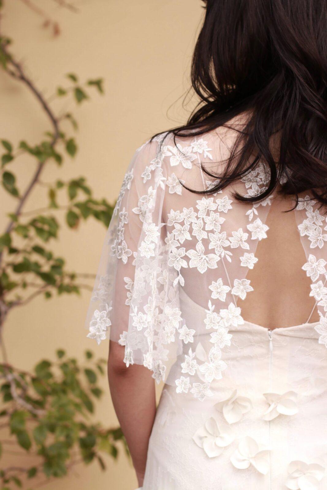 トレンドのスパゲティストラップのウェディングドレスに、トリートメゾンの小花のケープのようなボレロを合わせたおしゃれなコーディネート。