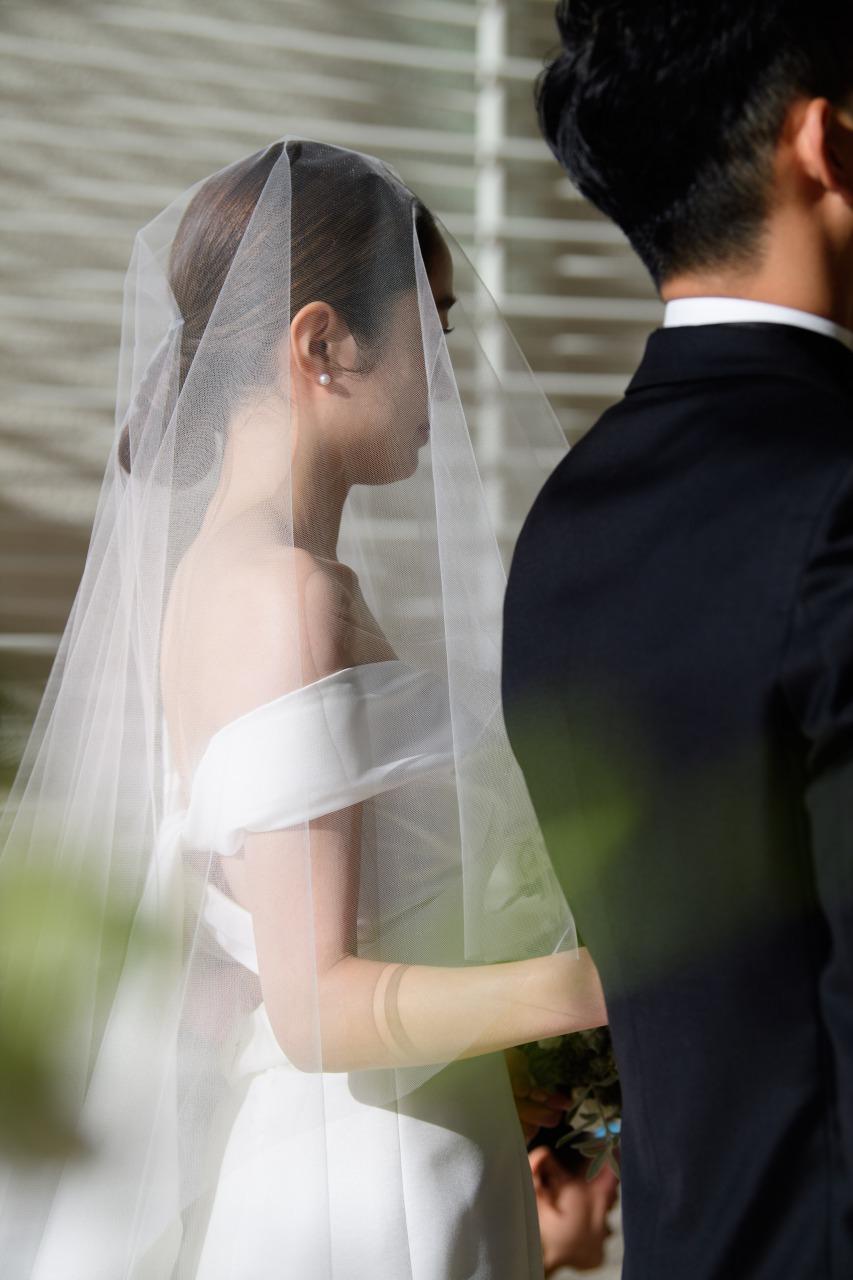オフショルダーと透明感のあるベールのコーディネートが美しい、パレスホテル東京で挙式をあげられたご新婦様。