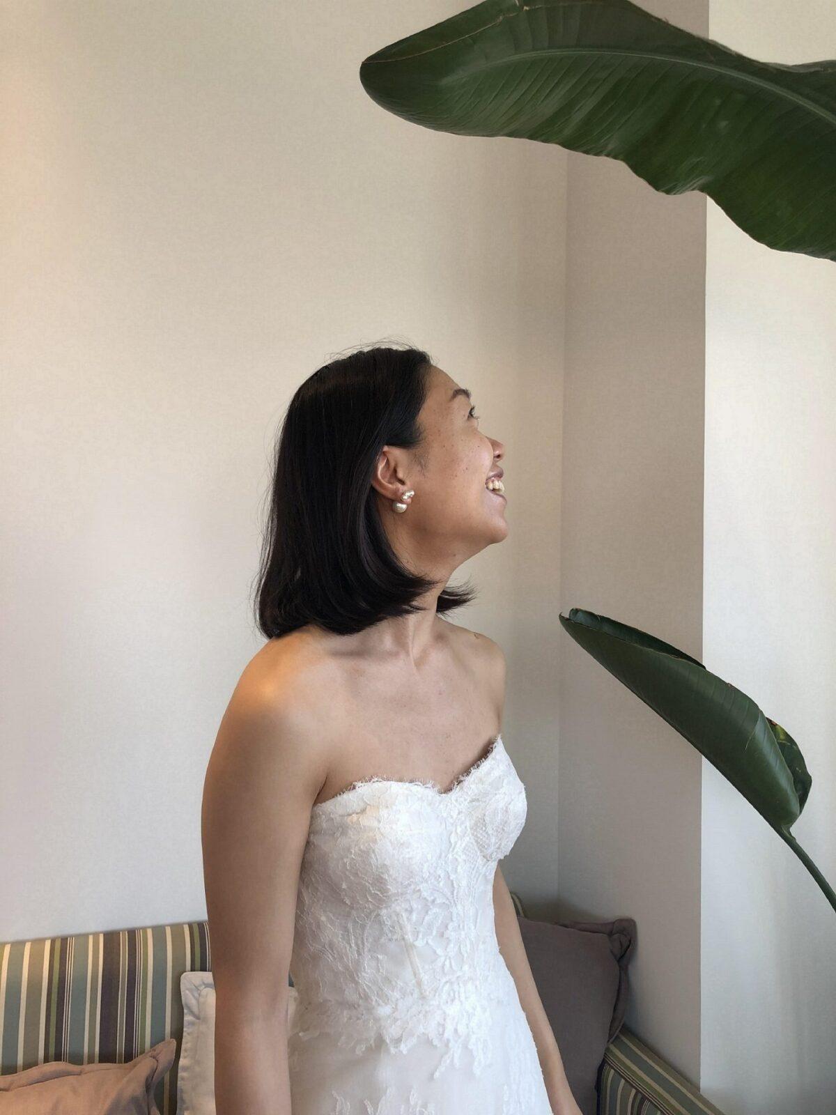 女性心をくすぐる美しいお花のレースが贅沢に全体にあしらわれた純白のレンタルウェディングドレスをまといアシンメトリーなパールのアクセサリーを合わせたお洒落なコーディネート。