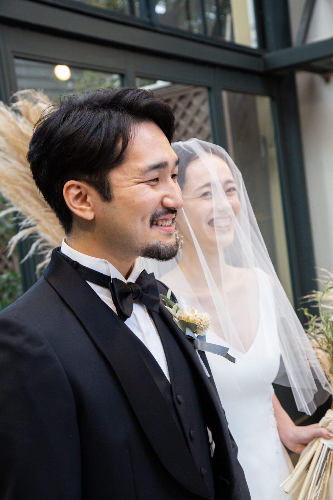 ウェディングドレスを纏ったご新婦様をエスコートするご新郎様の表情には、アットホームで賑やかな結婚式らしい自然体な笑顔が溢れます
