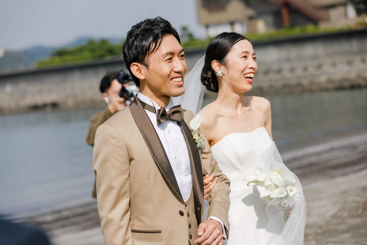 結婚式参列のゲストを前に新郎新婦の幸せな笑顔が溢れます
