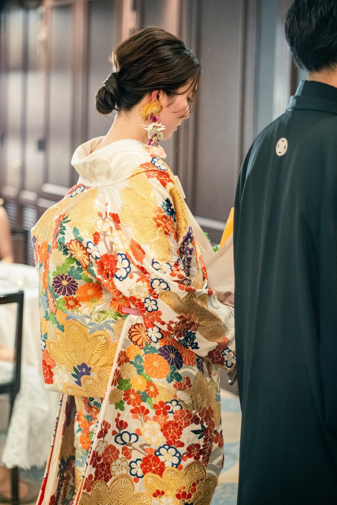 まとめたシニヨンに施された煌びやかな金箔は優美な印象を与えつつ、生花をアレンジしたいイヤリングで華やかさを演出した色打掛のコーディネート