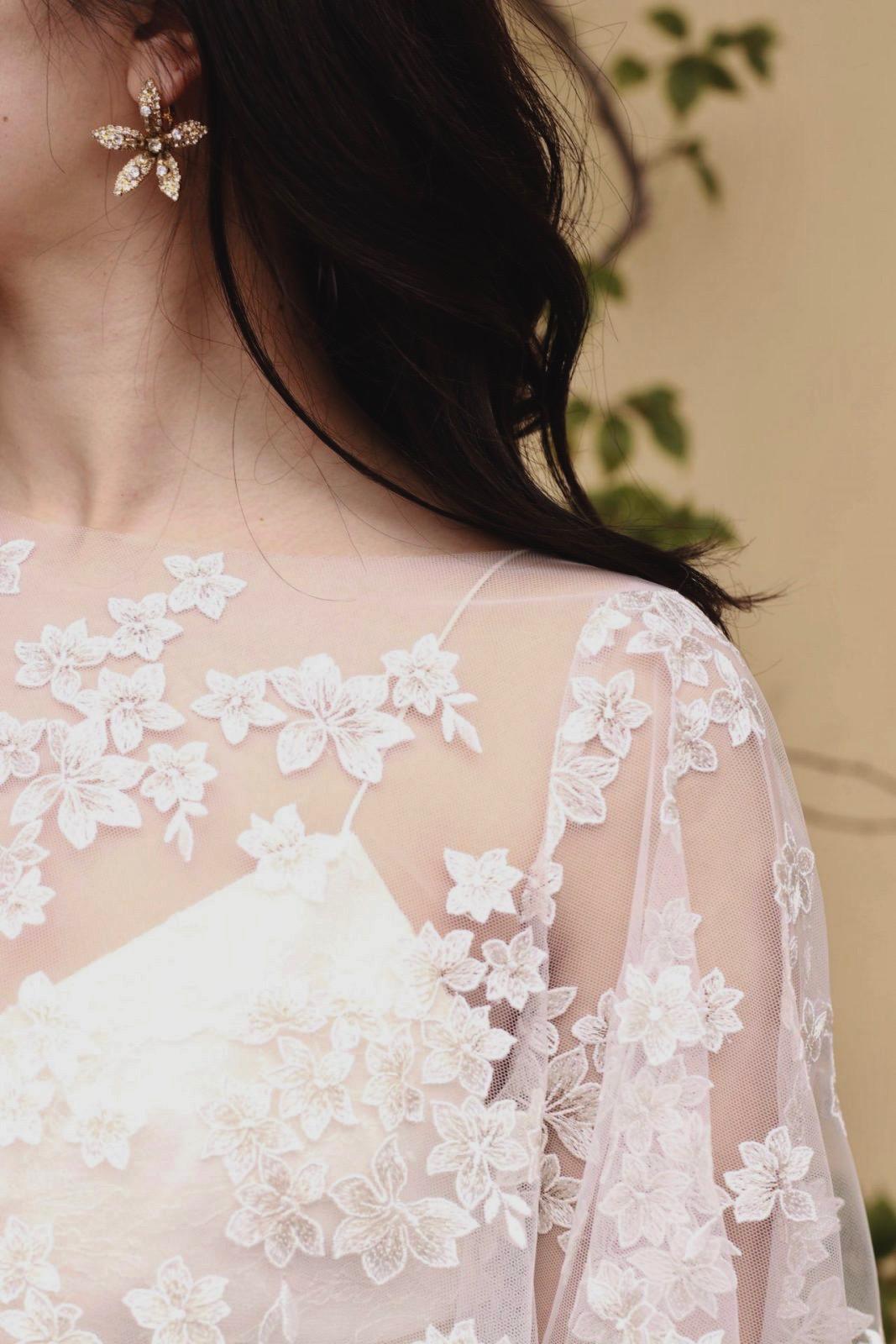 小花の美しいケープのようなボレロには、おしゃれ花嫁に人気のジェニファーベアのゴールドのイヤリングを合わせました。