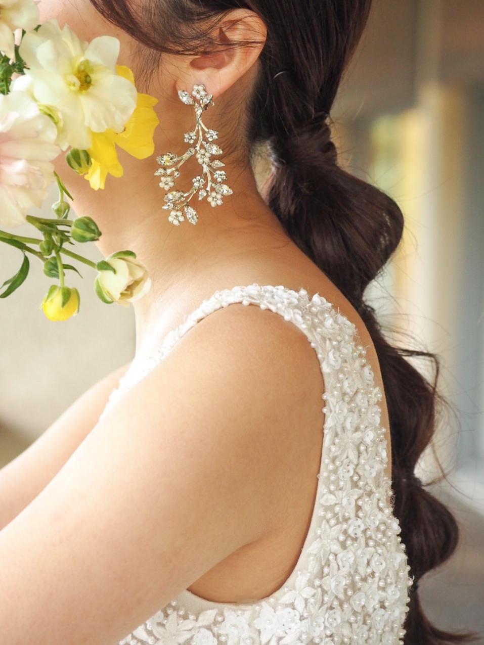 ザトリートドレッシング神戸店にてお取り扱いのあるリームアクラのフラワービジューが幻想的なウェディングドレスとリーフモチーフのイヤリングのコーディネート