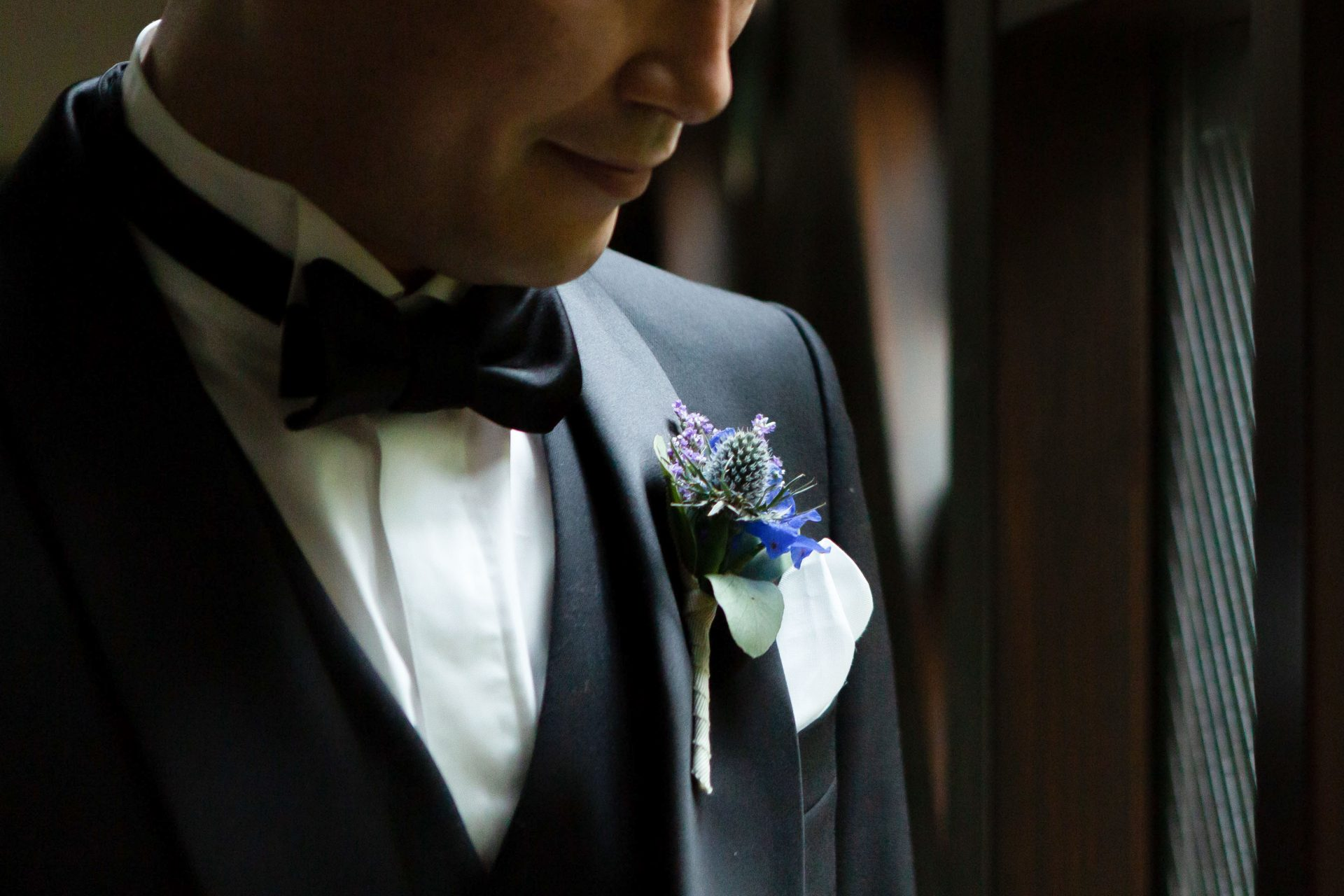 青色のブートニアが映えるブラックタキシードを身に纏ったご新郎様