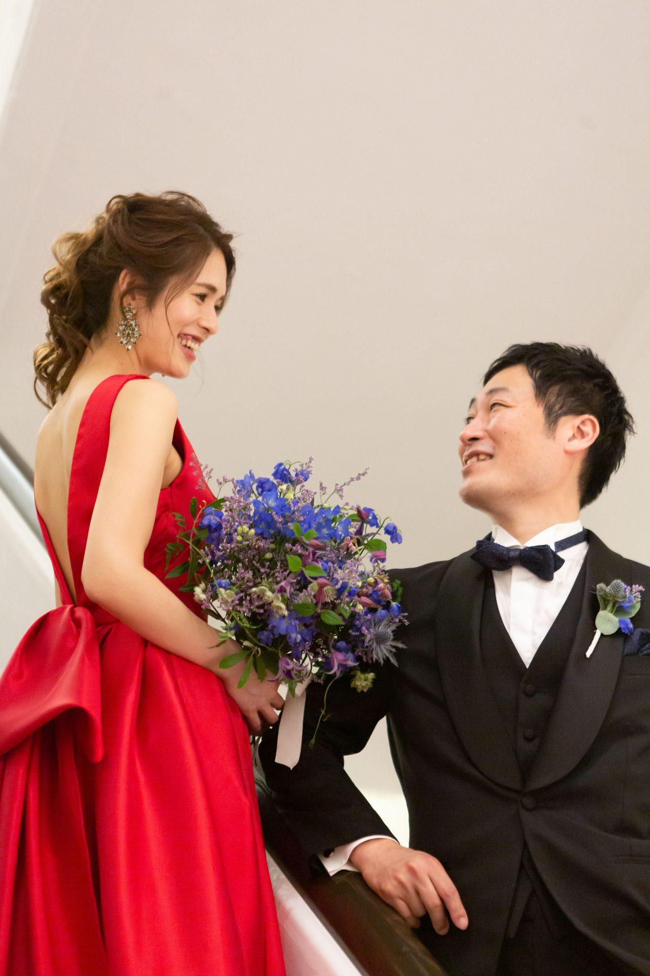 フォーチュンガーデン京都で前撮りをお考えのプレ花嫁様におすすめしたい鮮やかな赤色のカラードレスとスタイリッシュなブラックタキシード