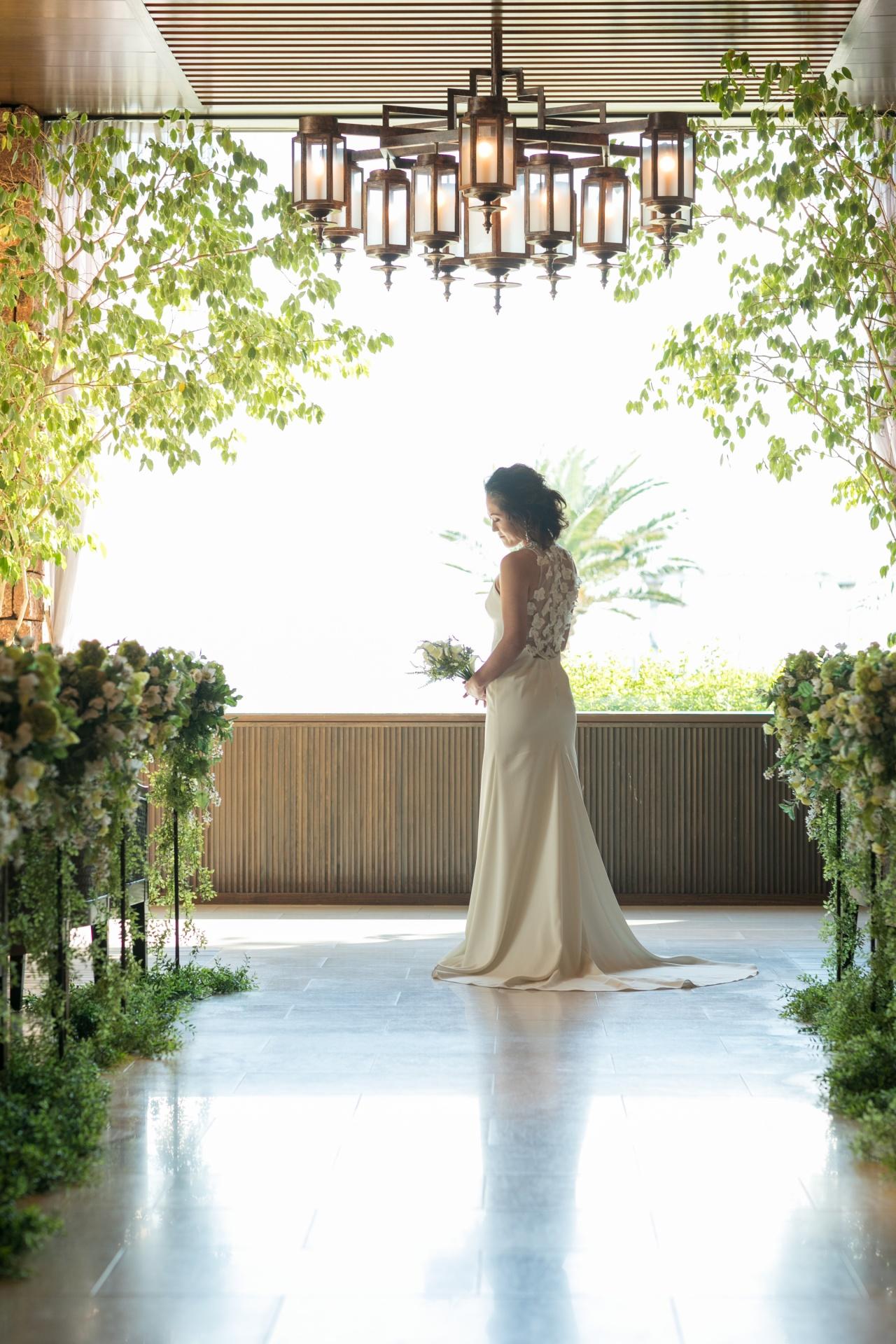 柔らかくとろみのあるバックトレーンが美しいウェディングドレスは、ザ・ルイガンズのチャペルの神秘的で爽やかな雰囲気にぴったり