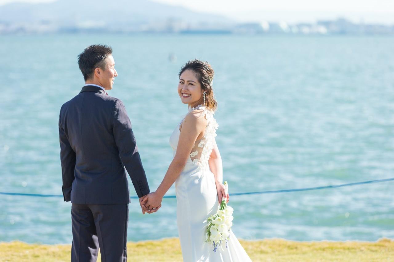 クレープ素材のスレンダードレスにバックスタイルは3Dフラワーが施された、シンプルながら遊び心のあるLela Rose(レラローズ)のレンタルウェディングドレス