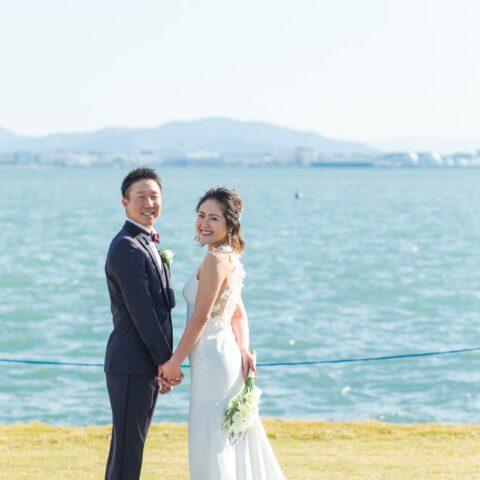 海とウェディングドレスのコントラストが美しい前撮り写真
