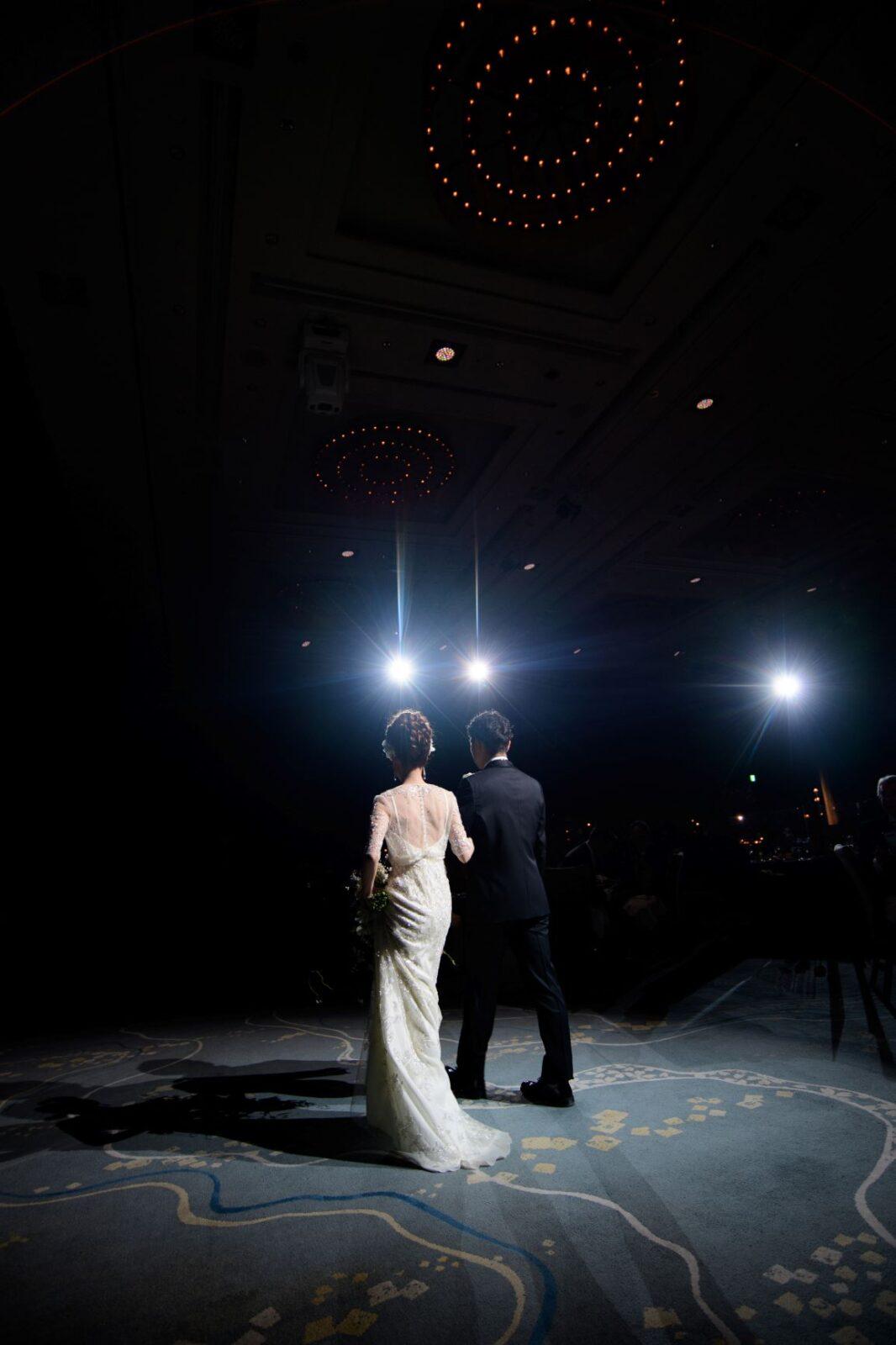 パレスホテル東京・葵西でのお色直しでジェニーパッカムのスレンダーラインのウェディングドレスとブラックフォーマルのタキシードを身に纏い、ご入場された新郎新婦様