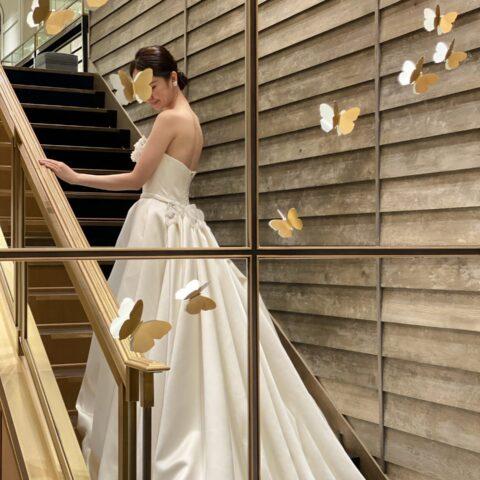 大きな階段に映えるトレーンが美しいウェディングドレス