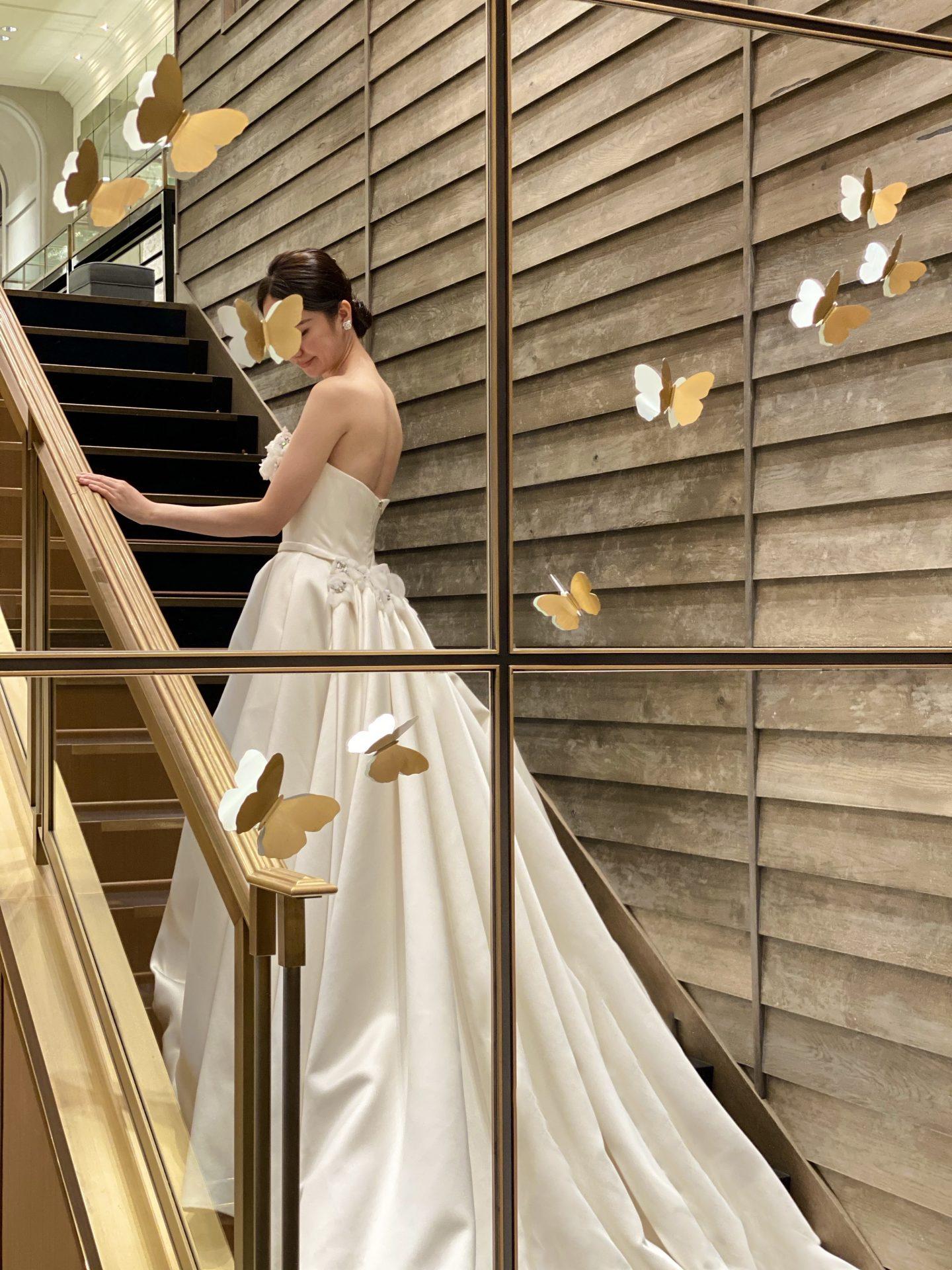 大きな階段のある結婚式場に映えるトレーンが美しいウェディングドレス