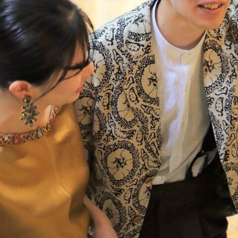 イエローのカラードレスの横に並ぶ新郎様の装いは、ブラウンのウェアを合わせ暖色系でまとめております。ジャケットは大胆な柄ですが、気品あるモダンな印象が特徴がスタイルに奥行を生みます。バンドカラーシャツを取り入れる事で、すっきりとした清涼感あるスタイルを演出します。
