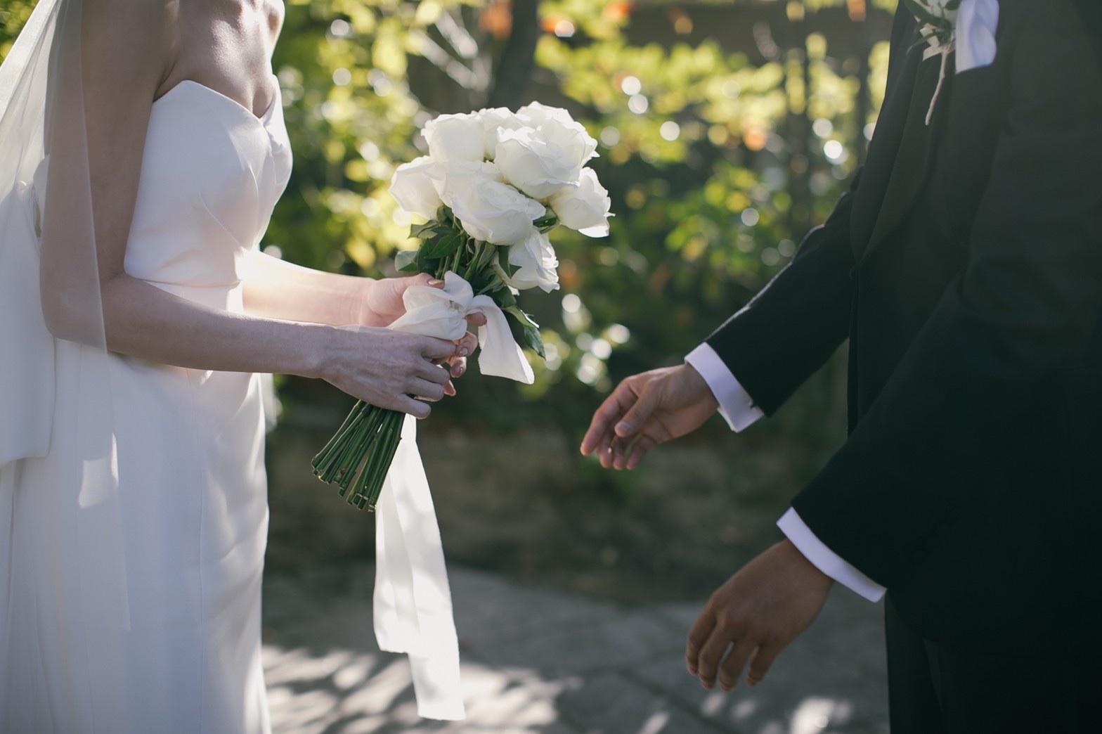 結婚式のブーケはシンプルな白のバラを束ねて洗練された雰囲気にする事でドレスとのバランスも美しくまとまります。