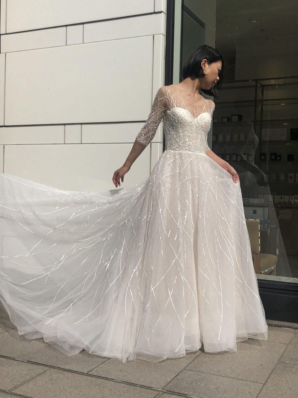 バーニーズニューヨーク横浜店で人気のレンタルウェディングドレスは直線状にビジューが施され、屋外では特にきらきらと美しく輝くハーフスリーブのAラインドレスです。