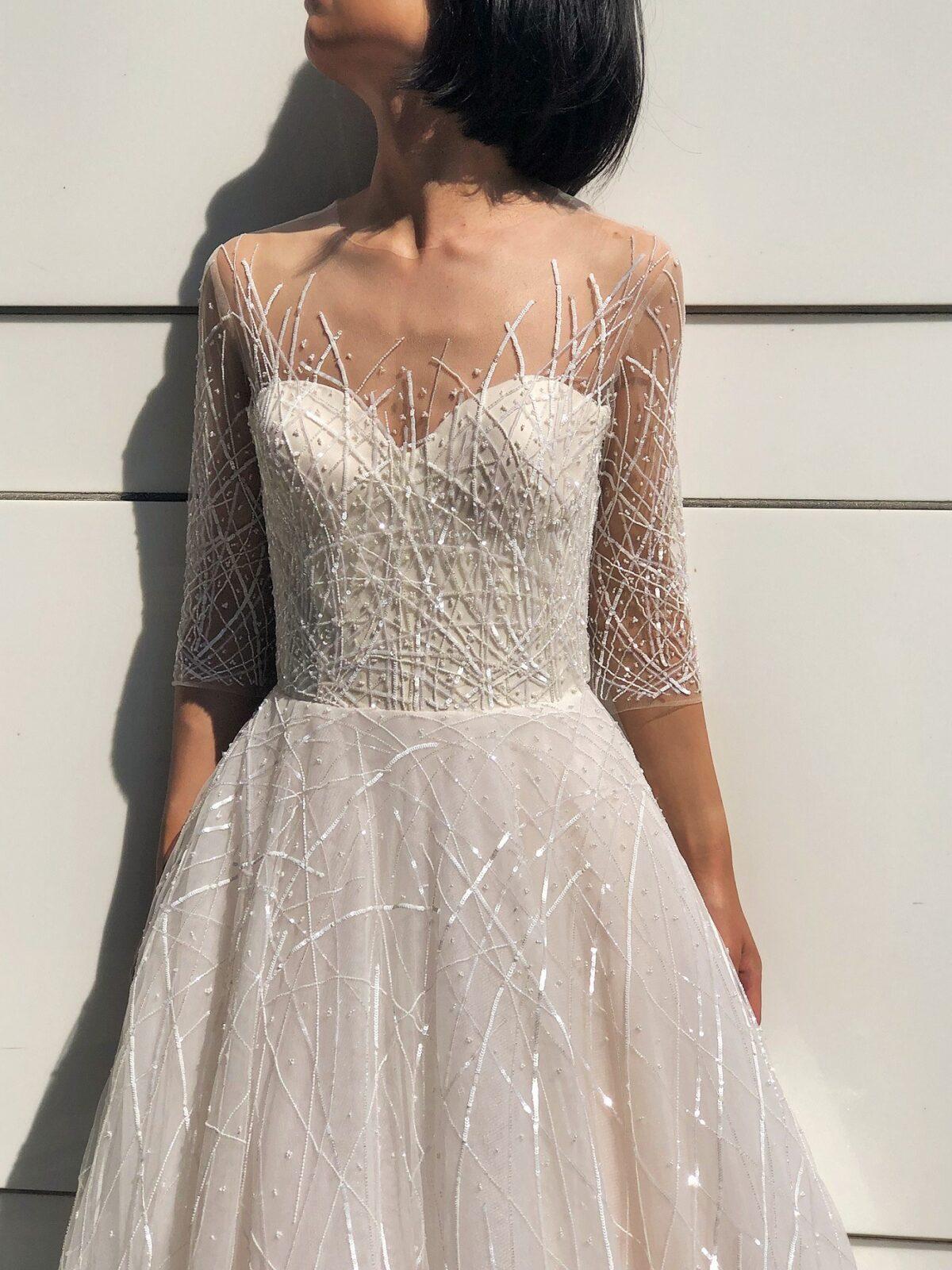 胸元とハーフスリーブにはチュールに魔法のようにちりばめられた直線状のスパンコールはお写真映りも申し分ない美しいレンタルウェディングドレスはElisabettaです。