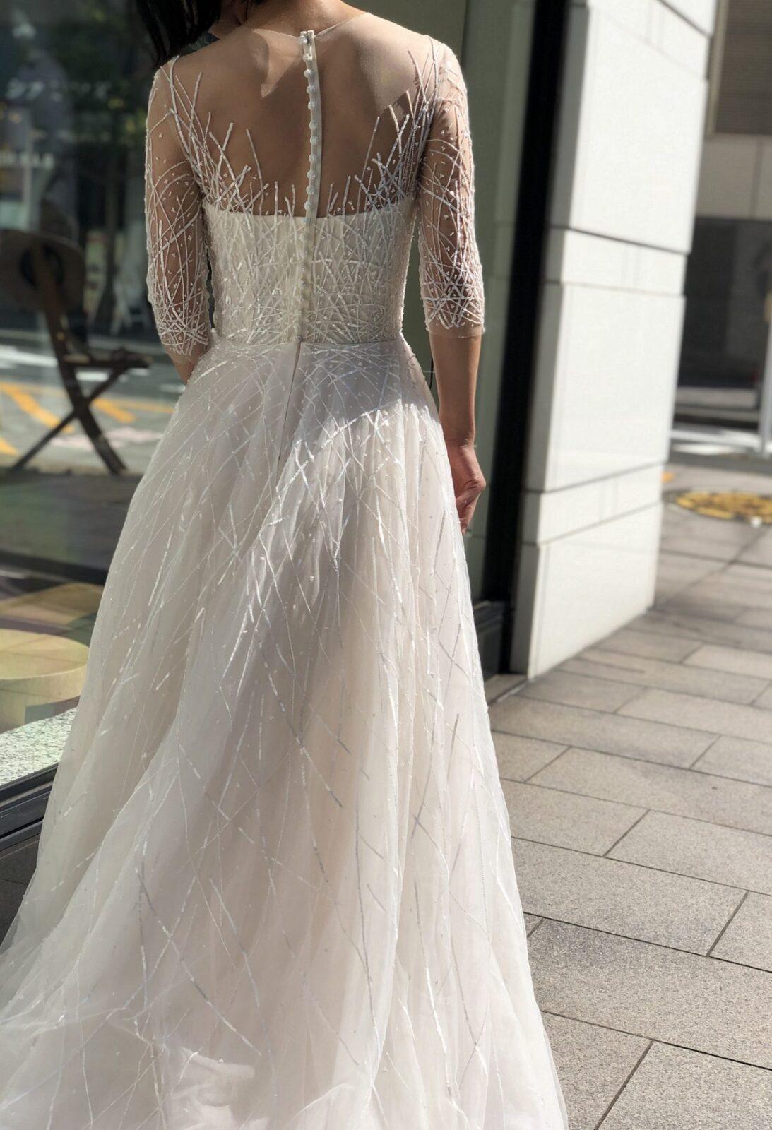 背中にあしらわれたくるみボタンとAラインシルエットがフェミニンさを演出するレンタルウェディングドレスはオシャレな花嫁様にお召しいただきたいトリートドレッシング横浜店のおすすめの1着です。