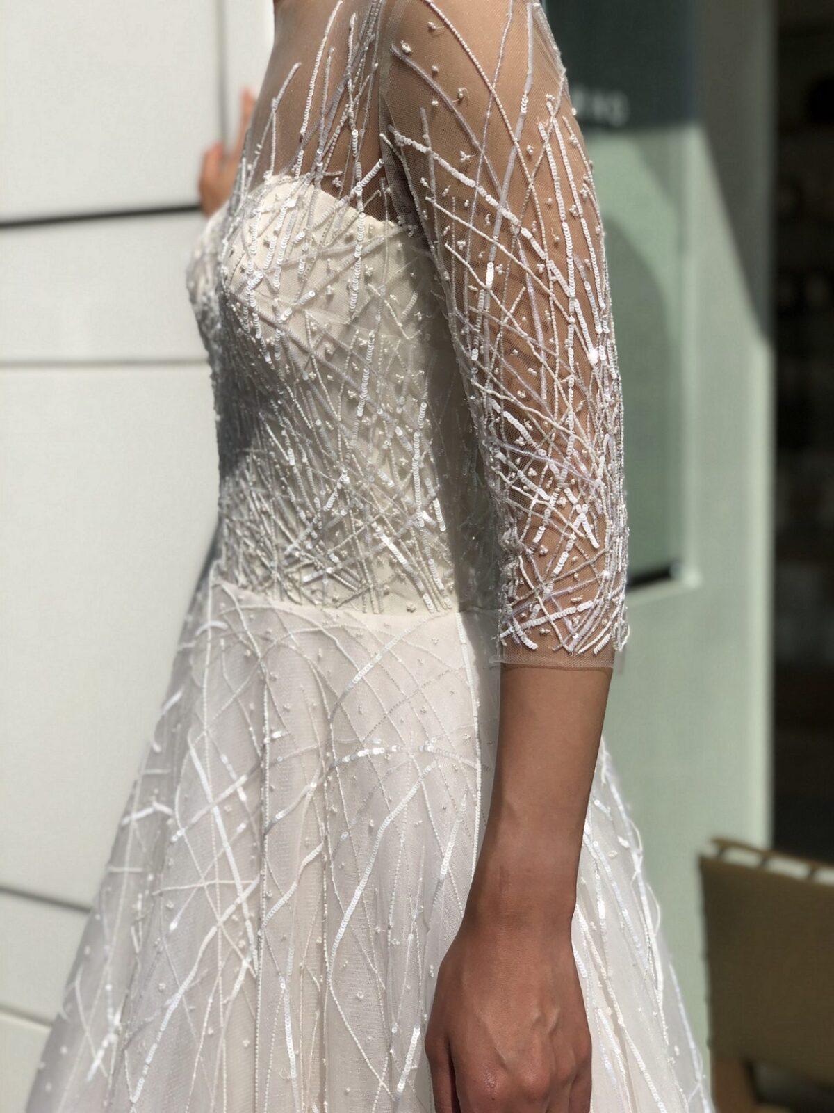 スパンコールで刺繍された直線に不規則にビーズが降りかけられたようにちりばめられたゴージャスなレンタルウェディングドレスで前撮りを楽しまれてはいかかでしょうか。