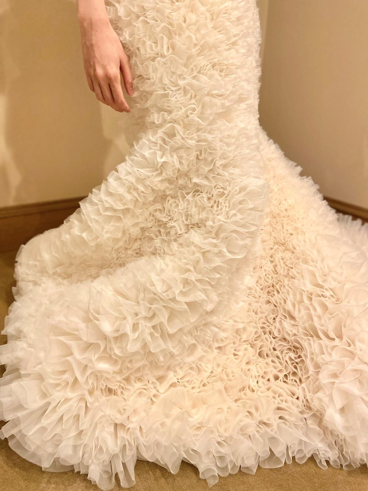 たっぷりと広がるフリルが美しいトモ コイズミのマーメイドのウェディングドレスは、ウィズザスタイルでのシックなパーティーにおすすめ