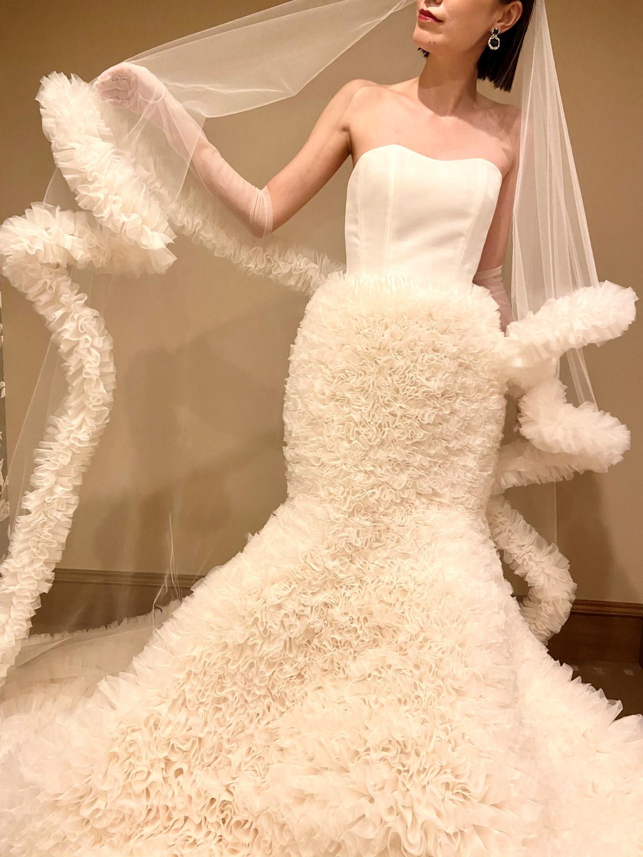 花びらのような大胆なフリルのシルエットは女性らしさとエレガントさをプラスラグジュアリーな結婚式にぴったり