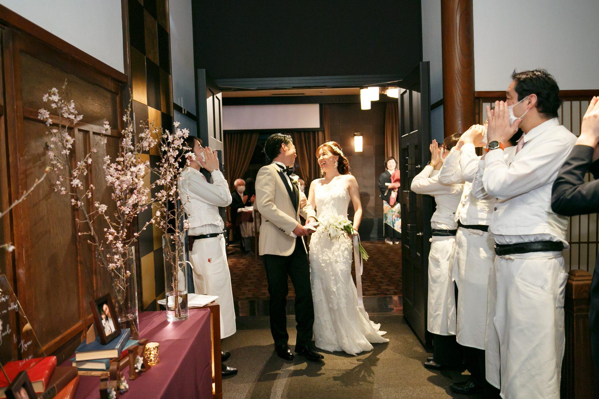 アイボリーのチェンジジャケットをお召しになったご新郎様とモニークルイリエのスレンダーラインのウェディングドレスをお召しになりスタッフの祝福に囲まれながら仲良く披露宴退場されるご新婦様