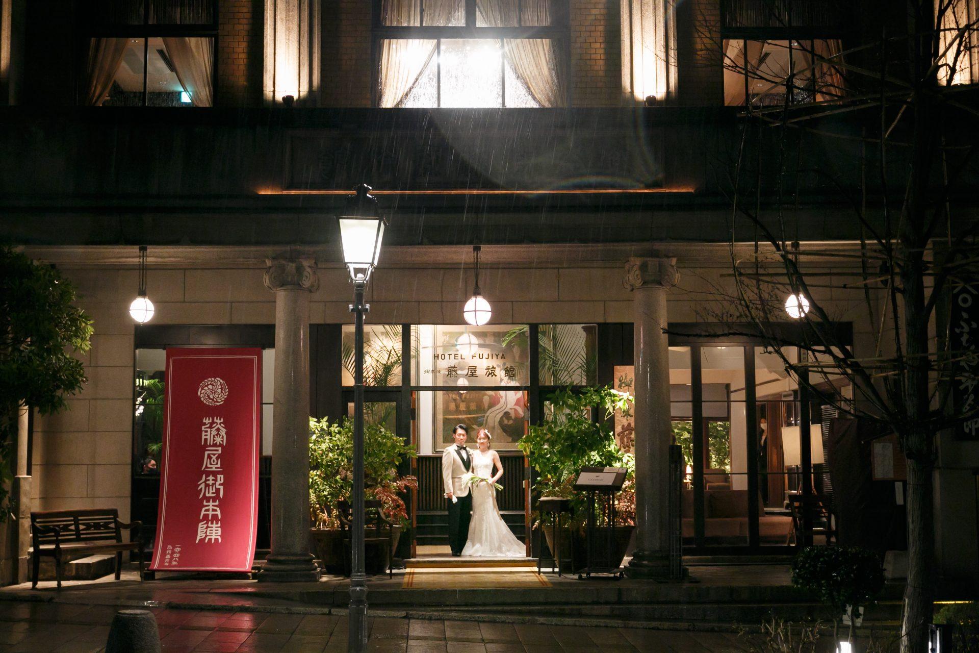 歴史的建造物である藤屋御本陳のエントランスでナイトウェディングならではのラストショットを撮影するご新郎ご新婦様