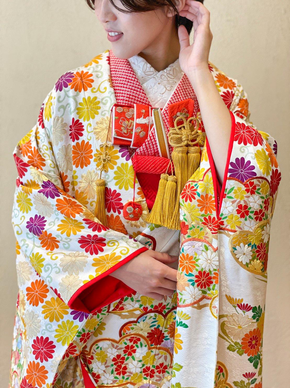 白色をベースに赤やオレンジ色の花がデザインされた色打掛には絞り染めの掛下を合わせてオシャレにコーディネート