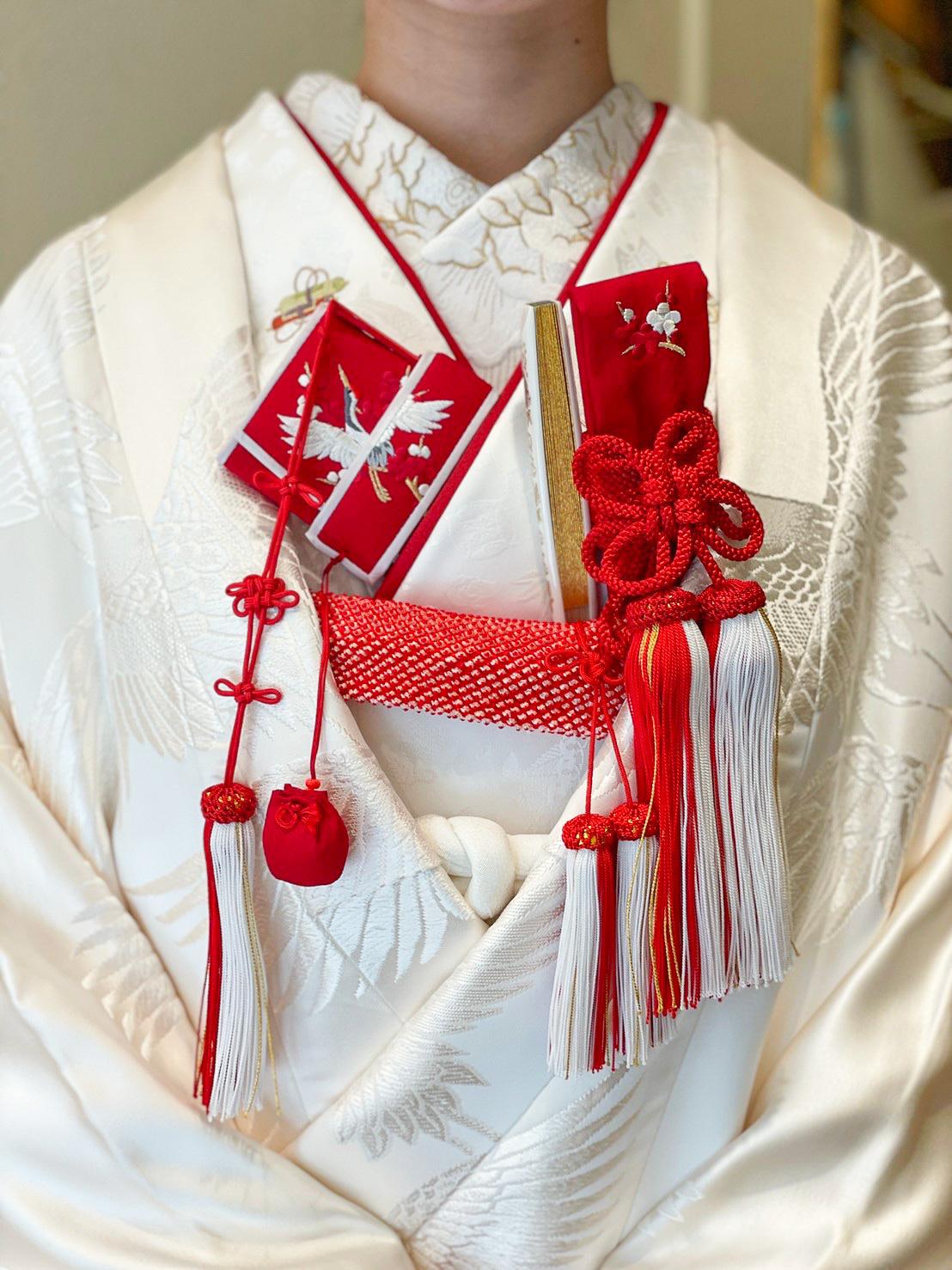 お色直しにもおすすめな白無垢の着こなし、昭和レトロな和装のコーディネートには鶴の白無垢に赤色の小物を合わせて結婚式を