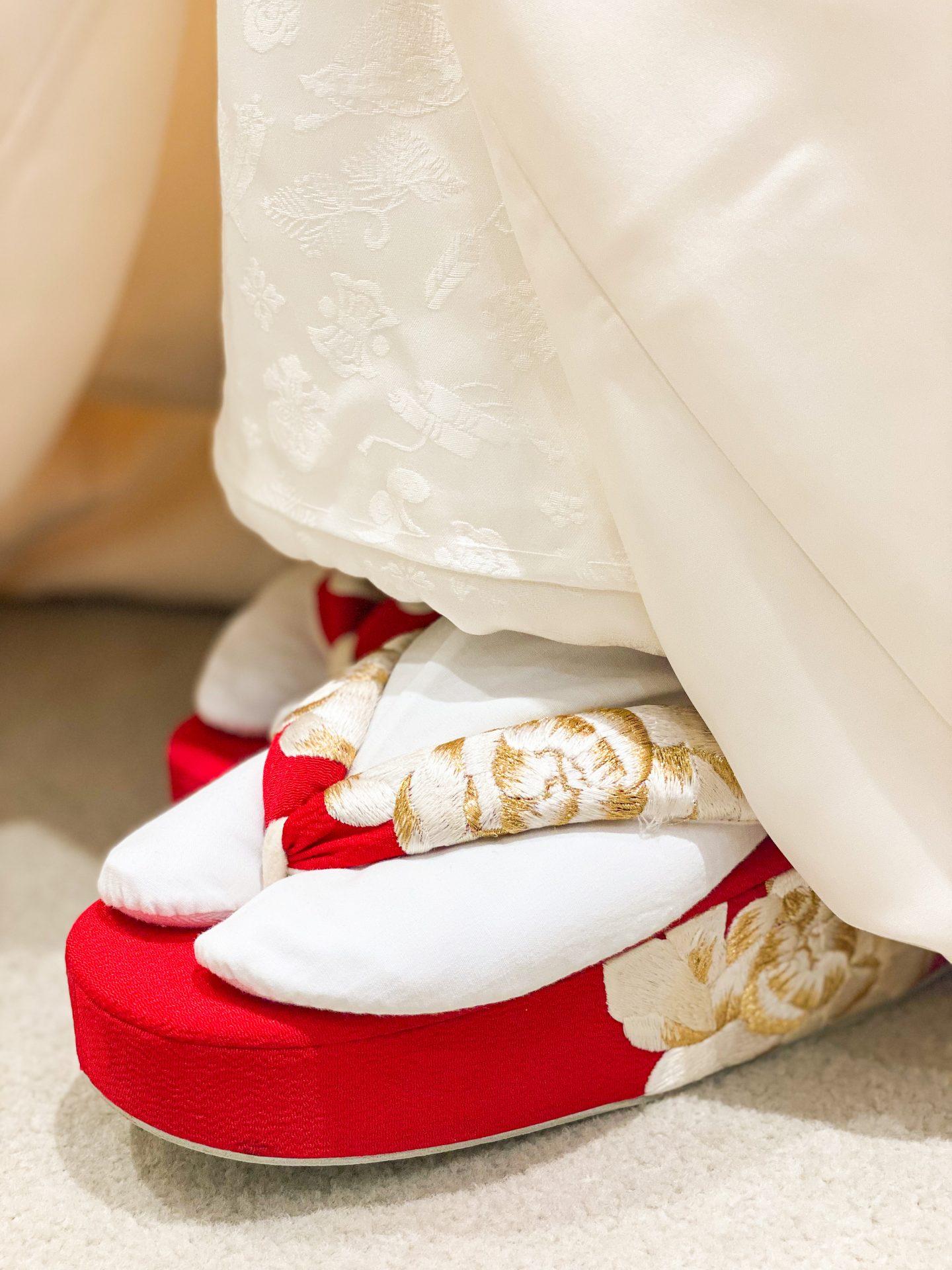 金糸の牡丹柄の刺繍が美しい赤の草履を白無垢に合わせる事で目を惹く存在に