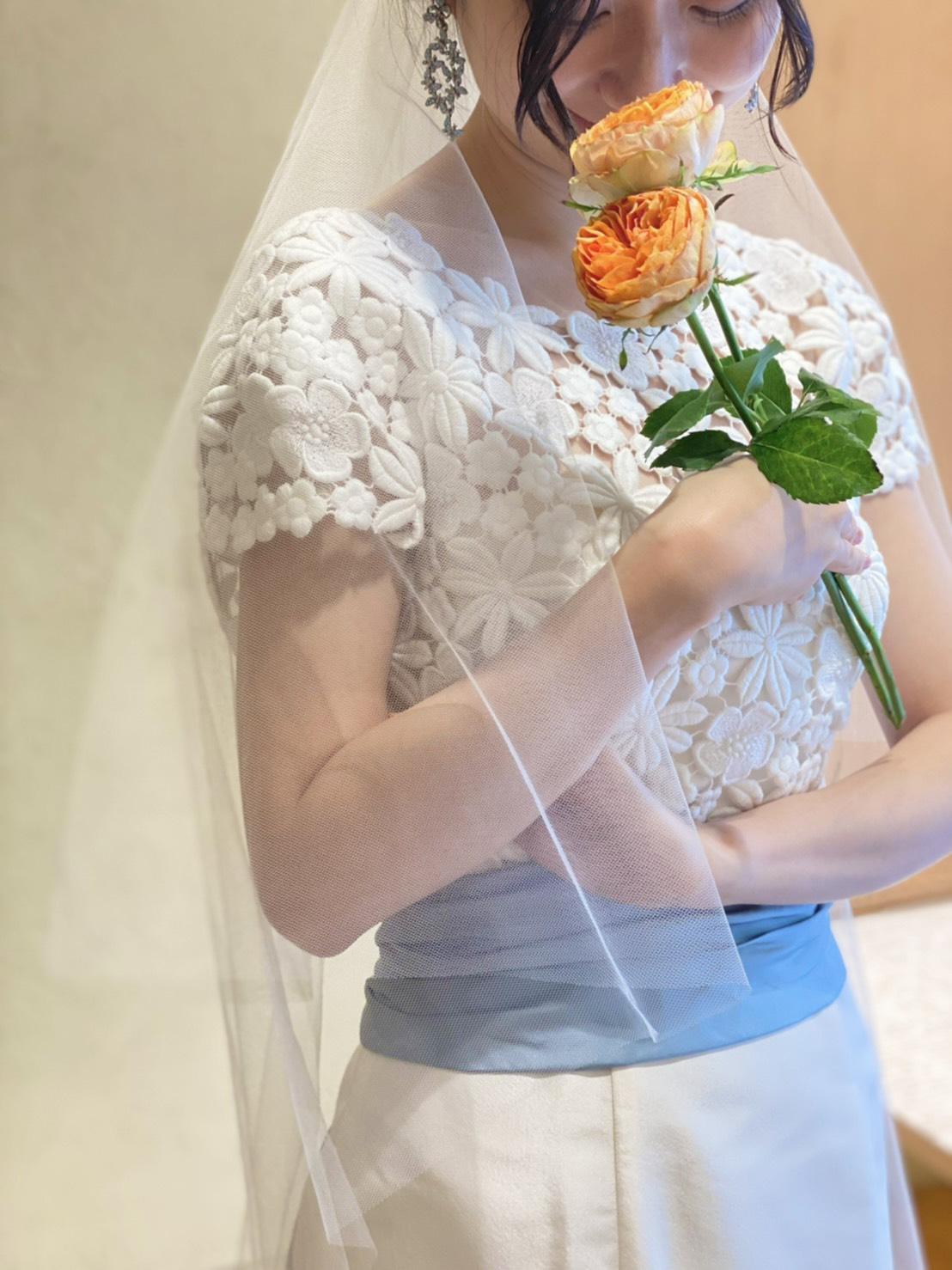 サムシングブルーのコーディネートにおすすめのブルーリボンがあしらわれたウエディングドレス