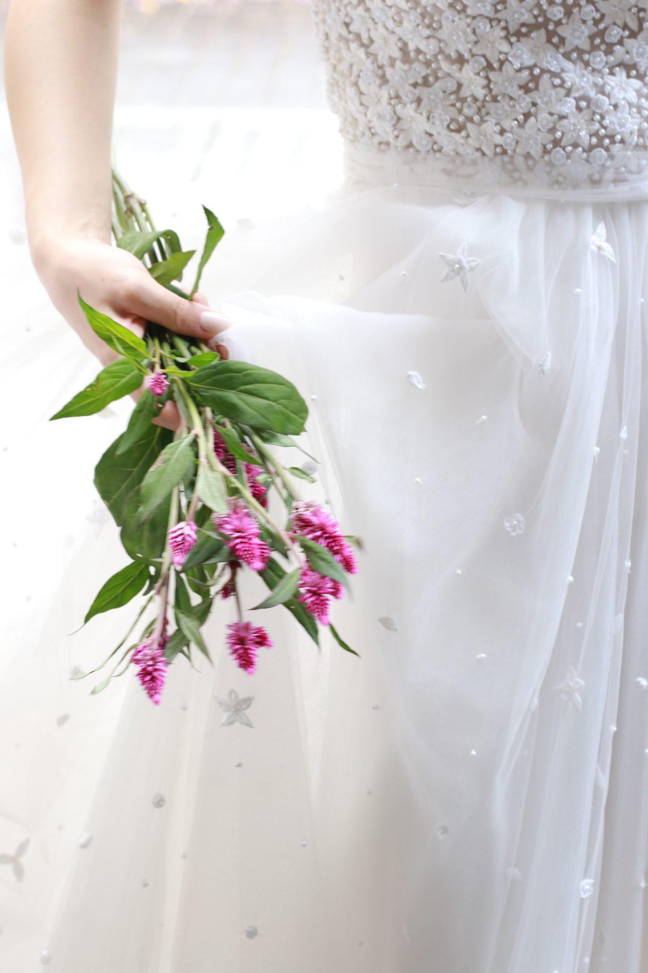 ふんだんにチュールを使用したAラインのウェディングドレスはグリーンと濃いめのピンクのお花を合わせていただくと柔らかい雰囲気を演出していただけます