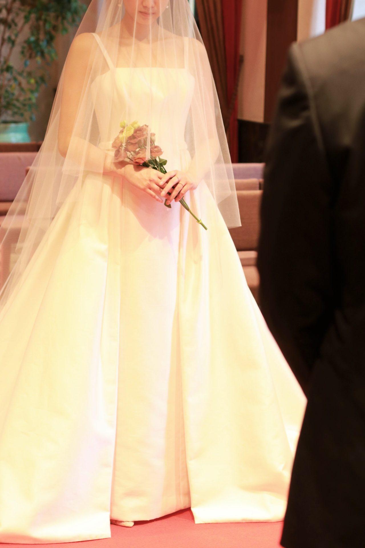 ザトリートドレッシングアディション店の提携会場、赤坂プリンスクラシックハウスのチャペルの赤絨毯のひかれたバージンロードをベールをまとった花嫁が歩みを進める姿に誰もが目を奪われます