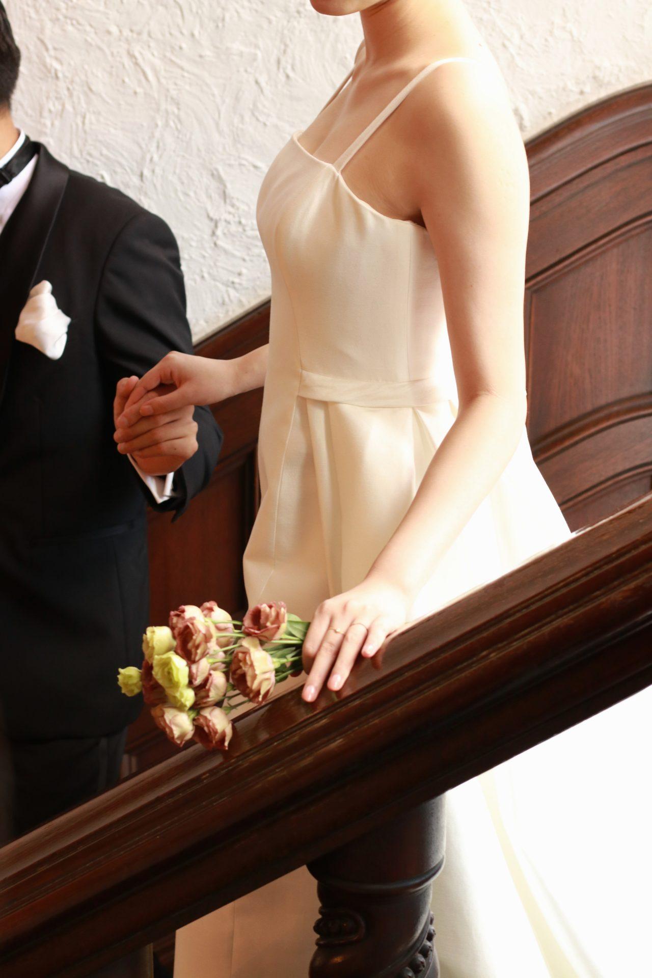 赤坂プリンスクラシックハウスのシンボルともいえるステンドグラスが印象的な木目調の階段をご新郎ご新婦様が手を取りあってモダンで洗練された披露宴会場へ向かいます