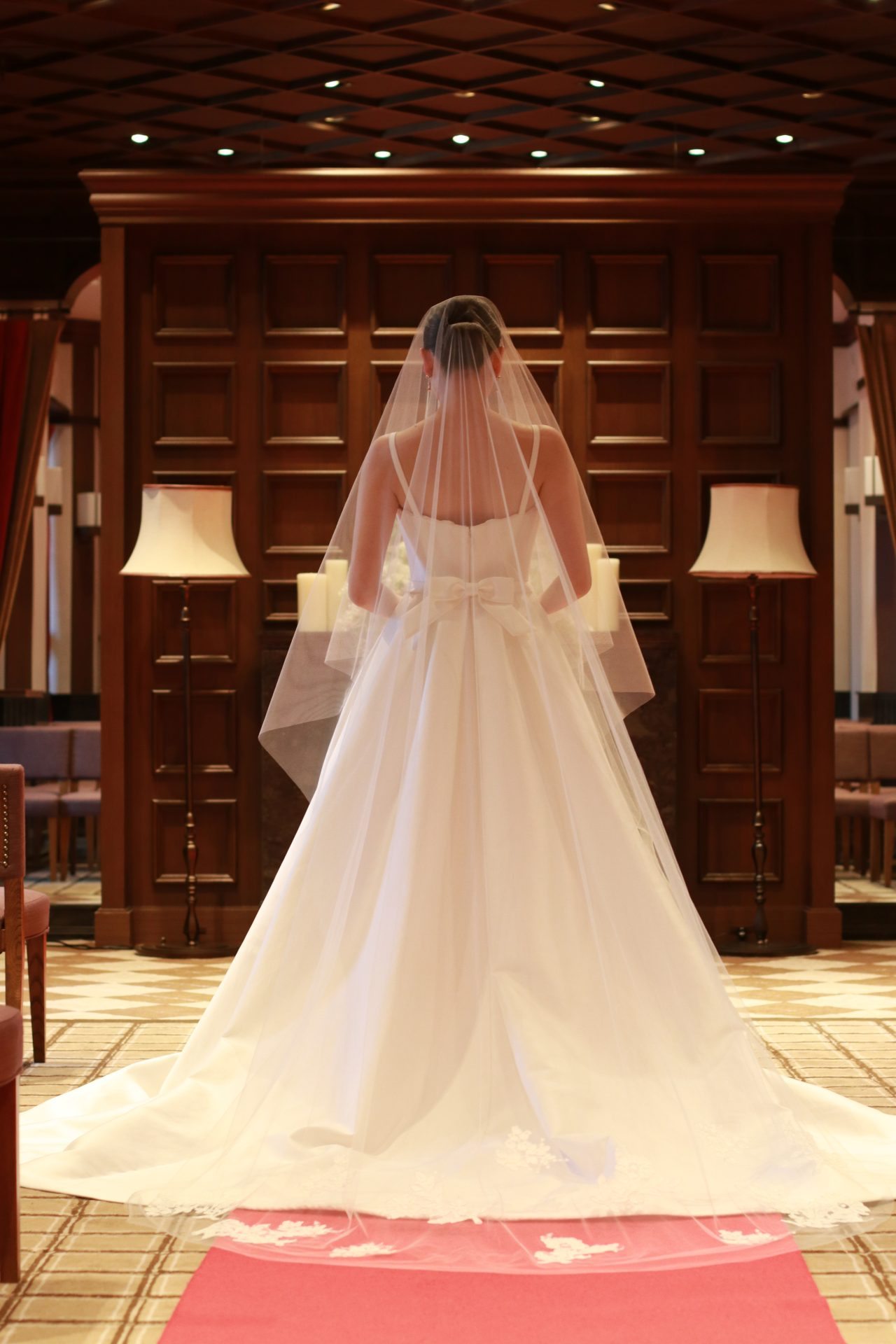 バックスタイルの腰元に施されたキャッチ―なリボンが印象的なシンプルなキャロリーナへレラのウェディングドレスには美しいコードリバーレースの施されたロングベールを合わせることで花を添えます