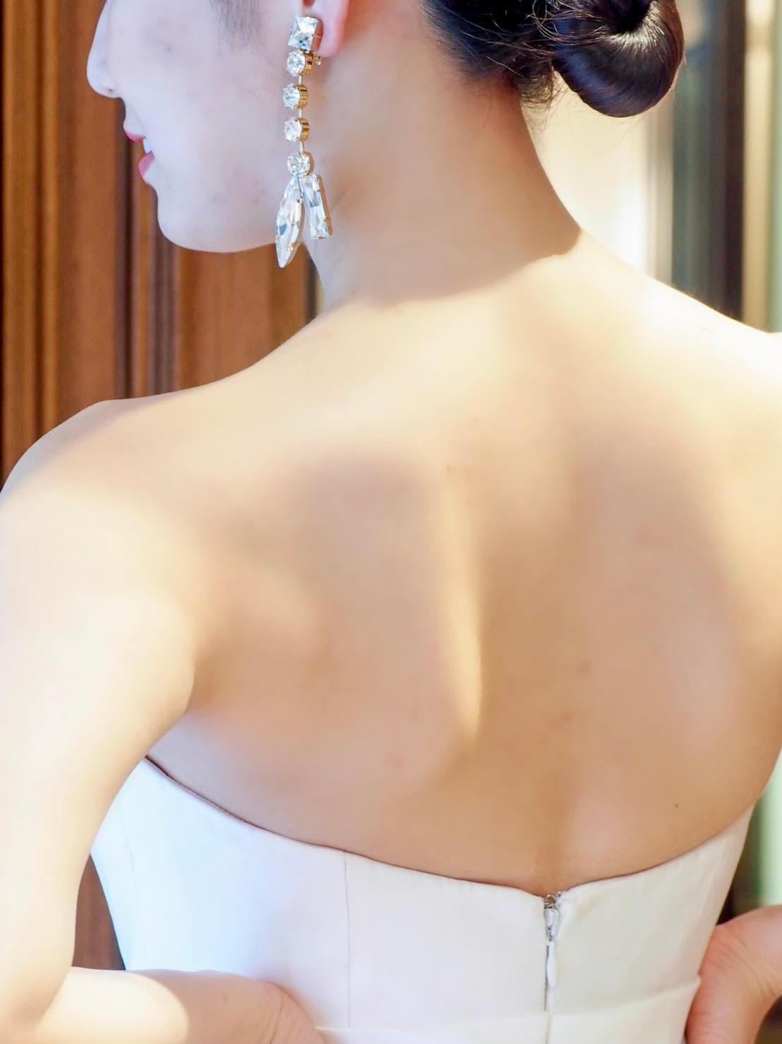 シンプルなドレスにぴったりのビッグイヤリングでコーディネートのポイントをおいたヴィクターアンドロルフマリアージュのウェディングドレス