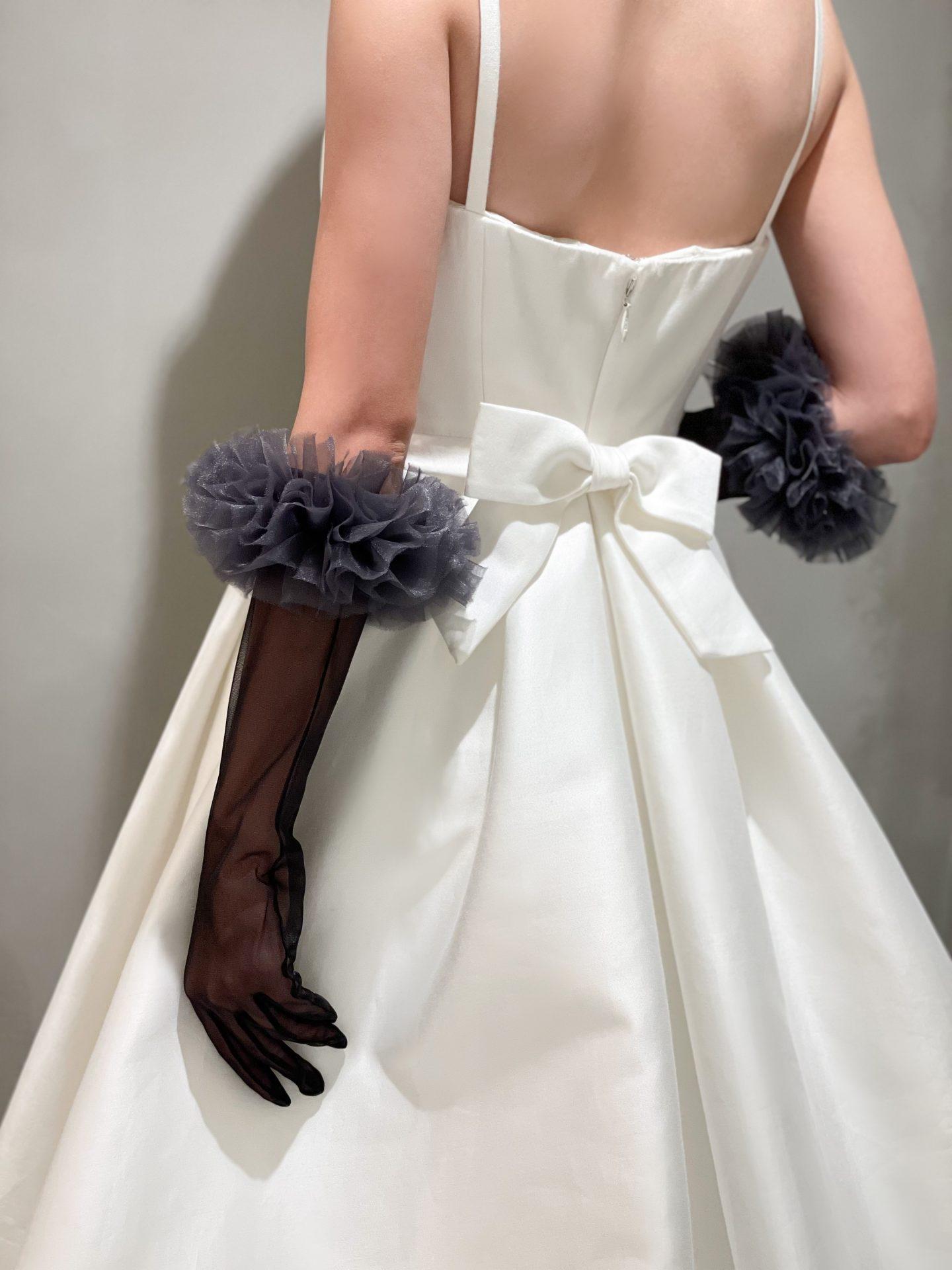 バックスタイルが美しいキャロリーナヘレラのウェディングドレスのコーディネートには黒のグローブを合わせて