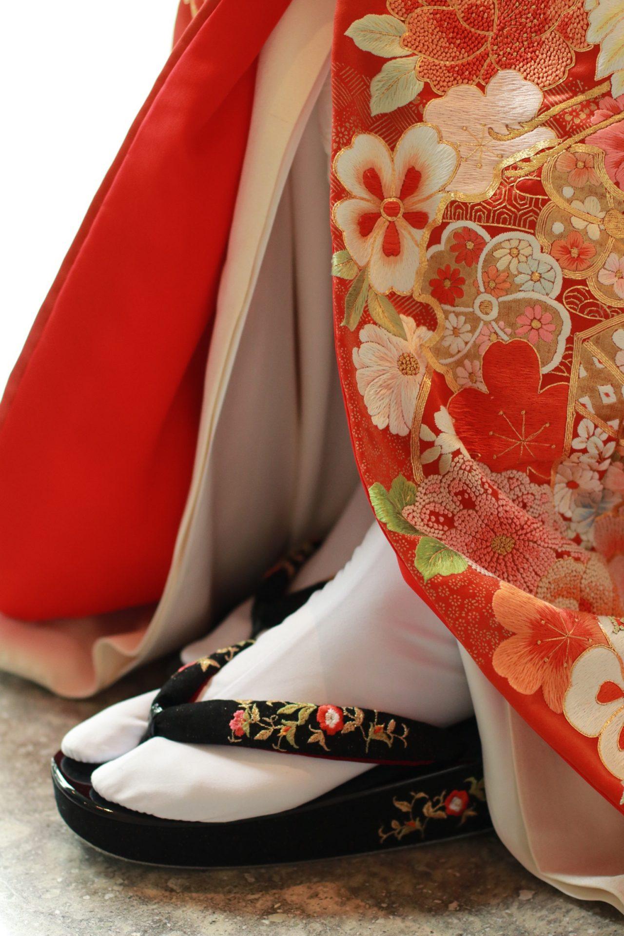 パレスホテル東京におすすめの赤の色打掛に、黒の草履を合わせたモダンなコーディネート提案
